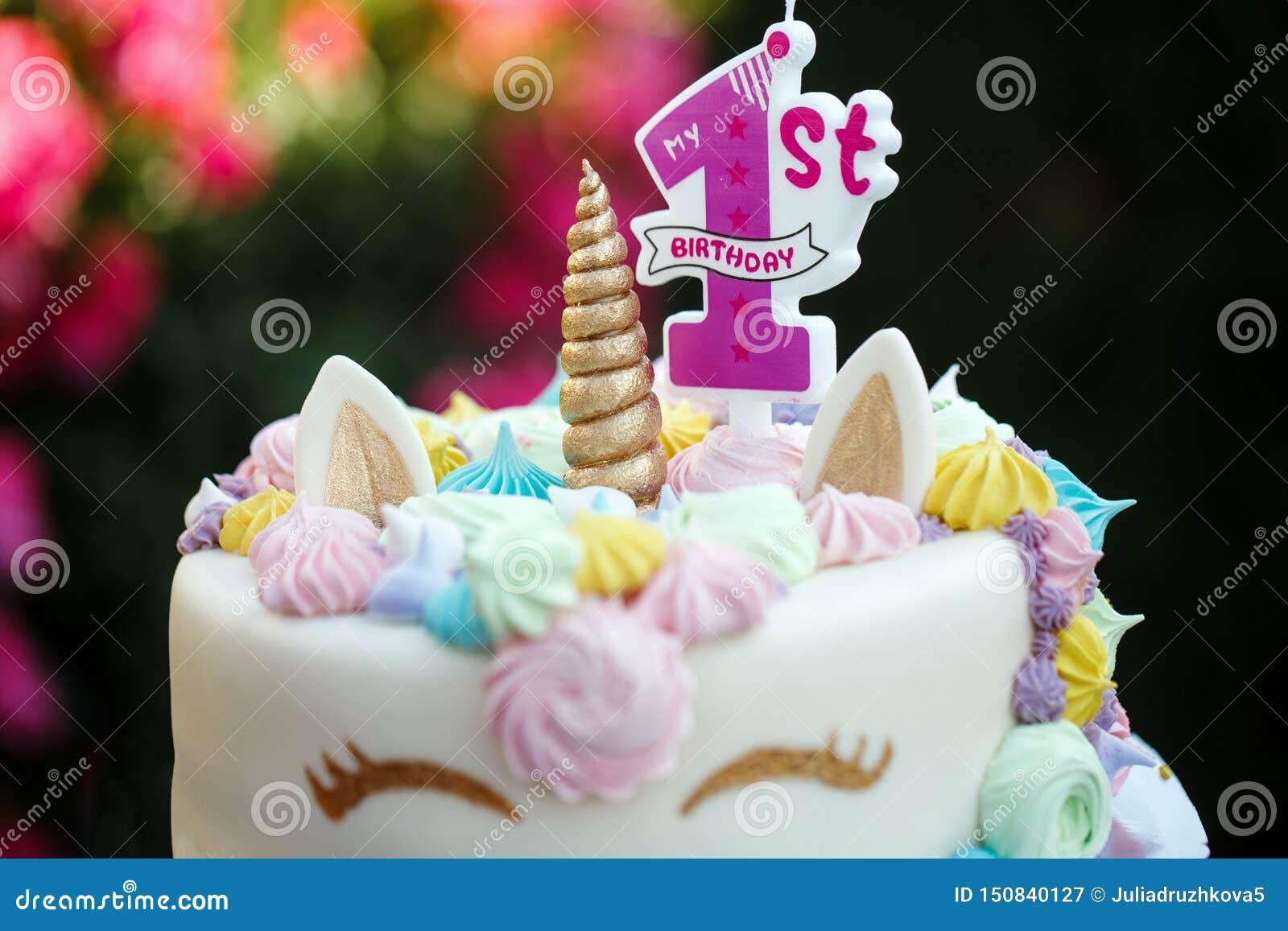 Torta con un unicornio para 1 cumpleaños, un día de fiesta de los niños en naturaleza