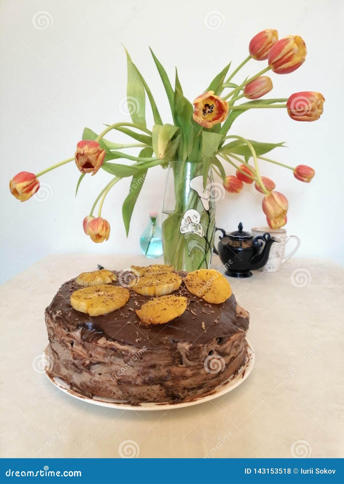 Torta de chocolate adornada con las naranjas en el fondo de tulipanes