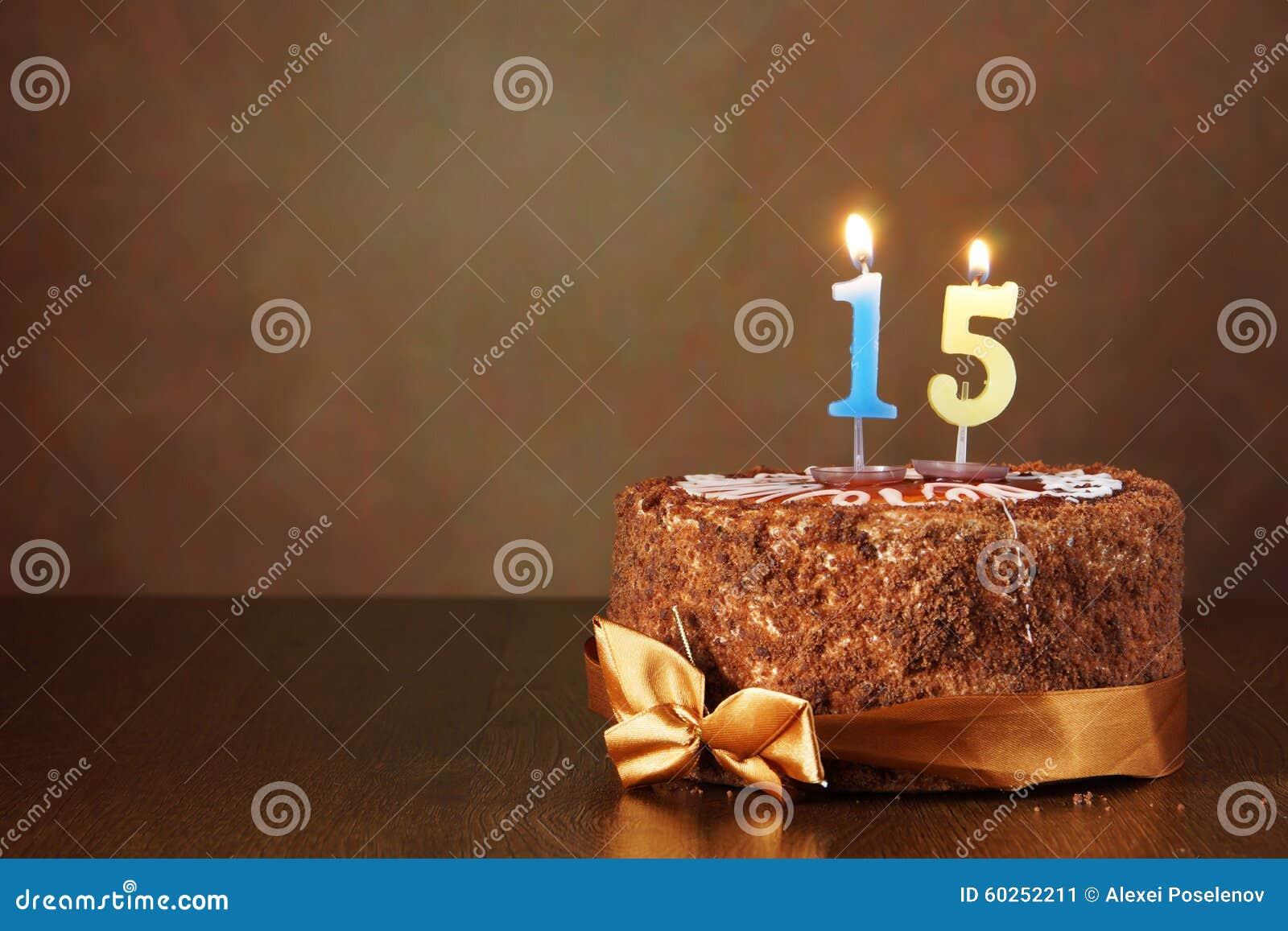Torta de chocolate del cumpleaños con las velas ardientes como número quince