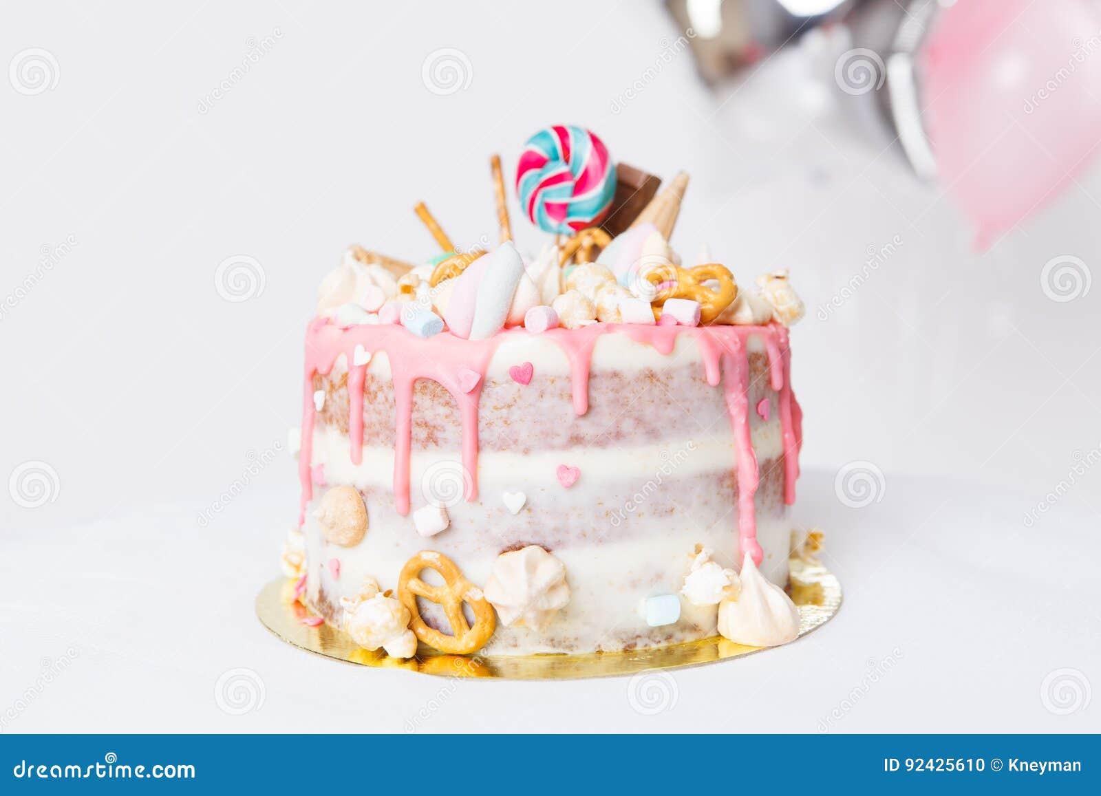 Torta de cumpleaños con adornado con los caramelos, piruleta, melcochas Color en colores pastel rosado Globos en fondo