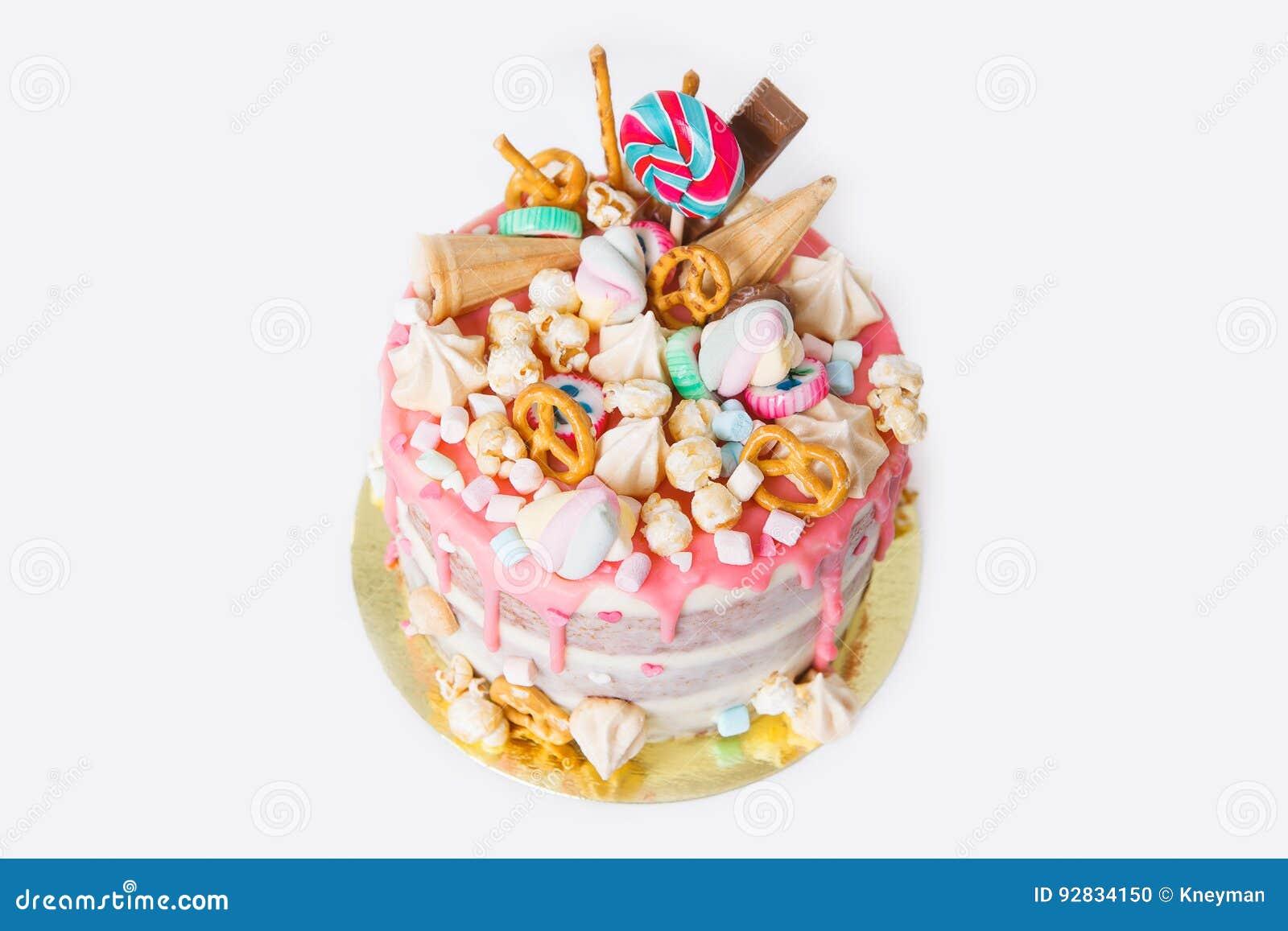 Torta de cumpleaños con adornado con los caramelos, piruleta, melcochas Color en colores pastel rosado Globos en fondo Aislado