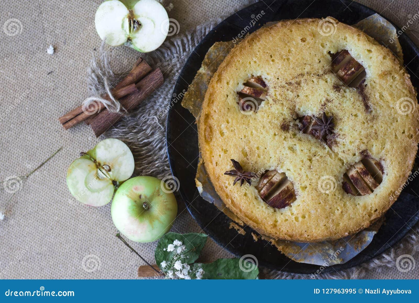 Torta del canela de Apple, palillos de canela, manzanas en la endecha del plano de la tabla
