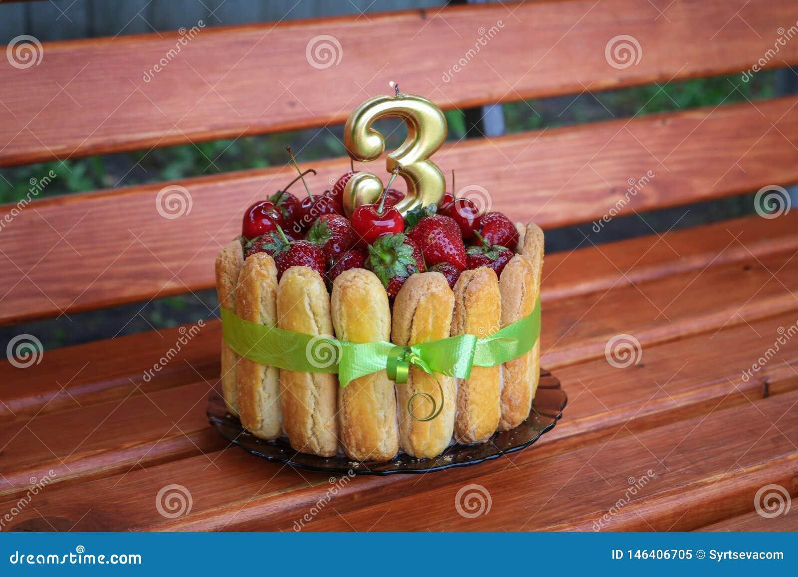 Torta di compleanno con le fragole e le ciliege su un fondo di legno