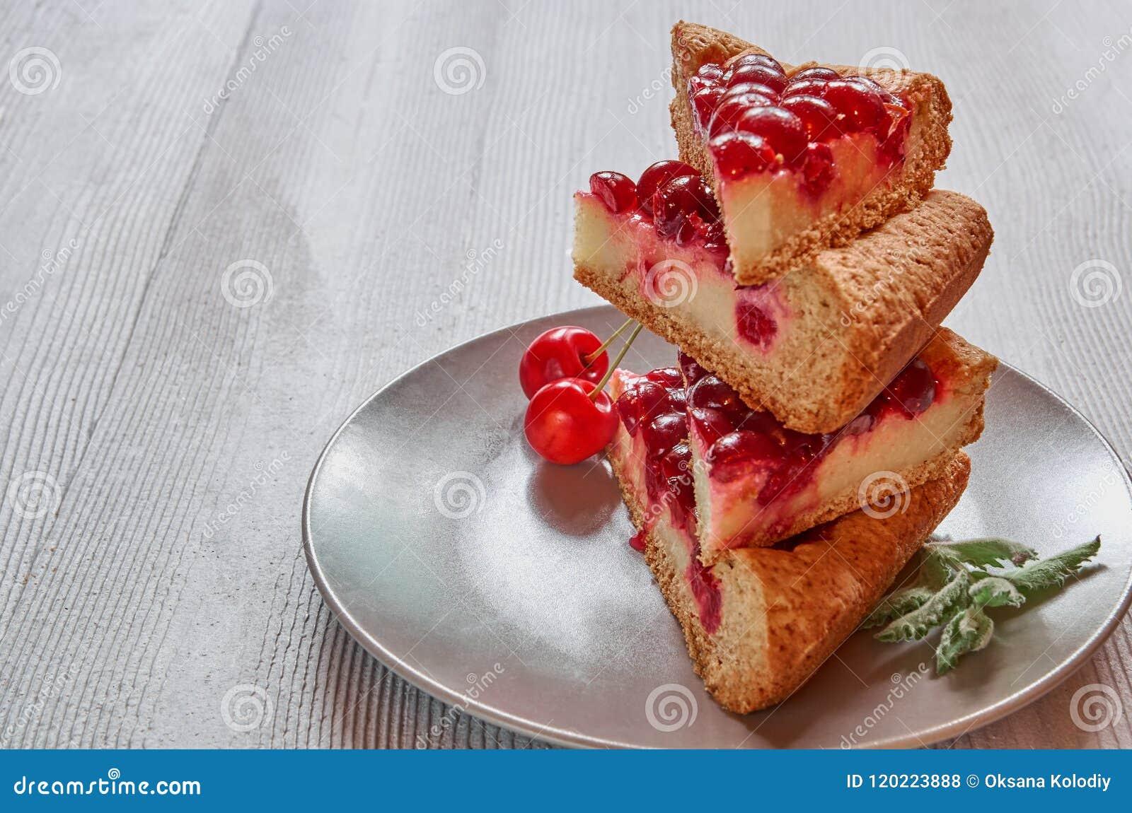 Torta di formaggio affettata della ciliegia con gelatina sul piatto grigio con lo spazio della copia per testo Pezzi di crostata