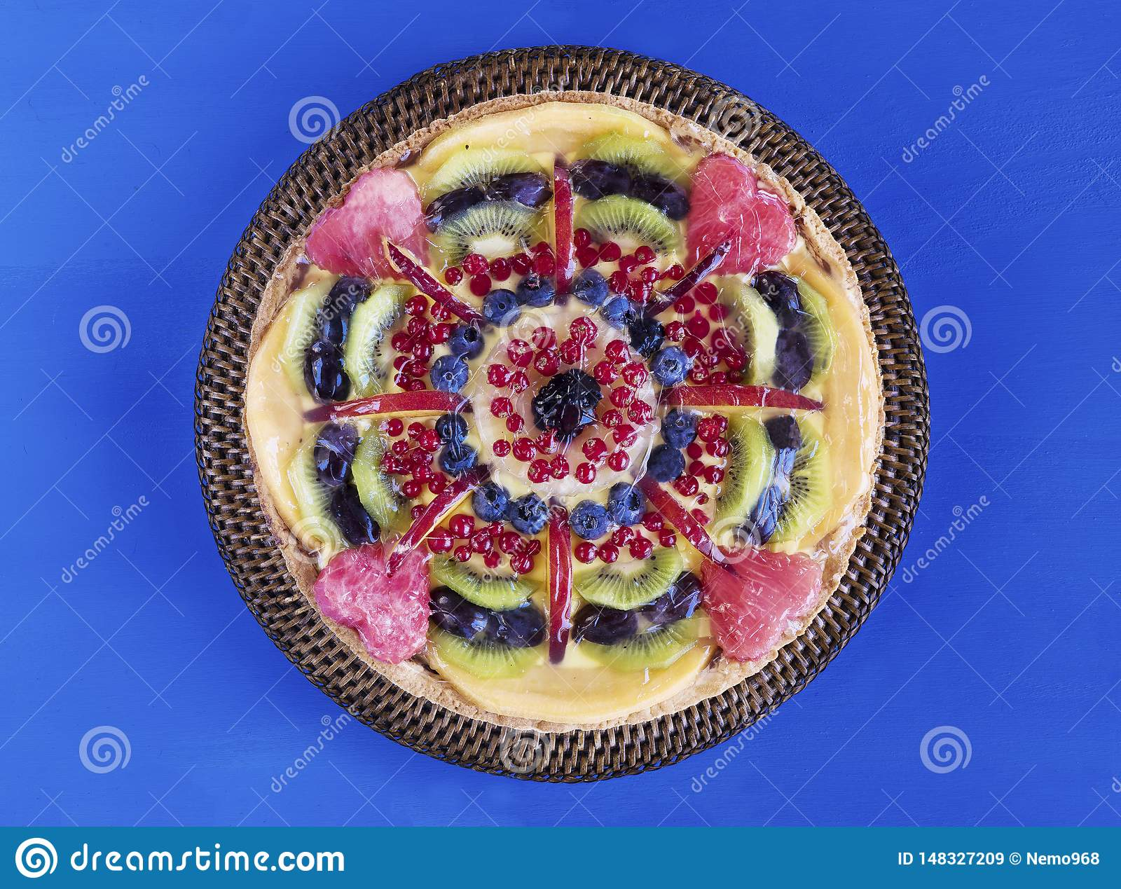 Torta di frutta con crema e le bacche sul supporto del dolce, sui fiori e sull asciugamano