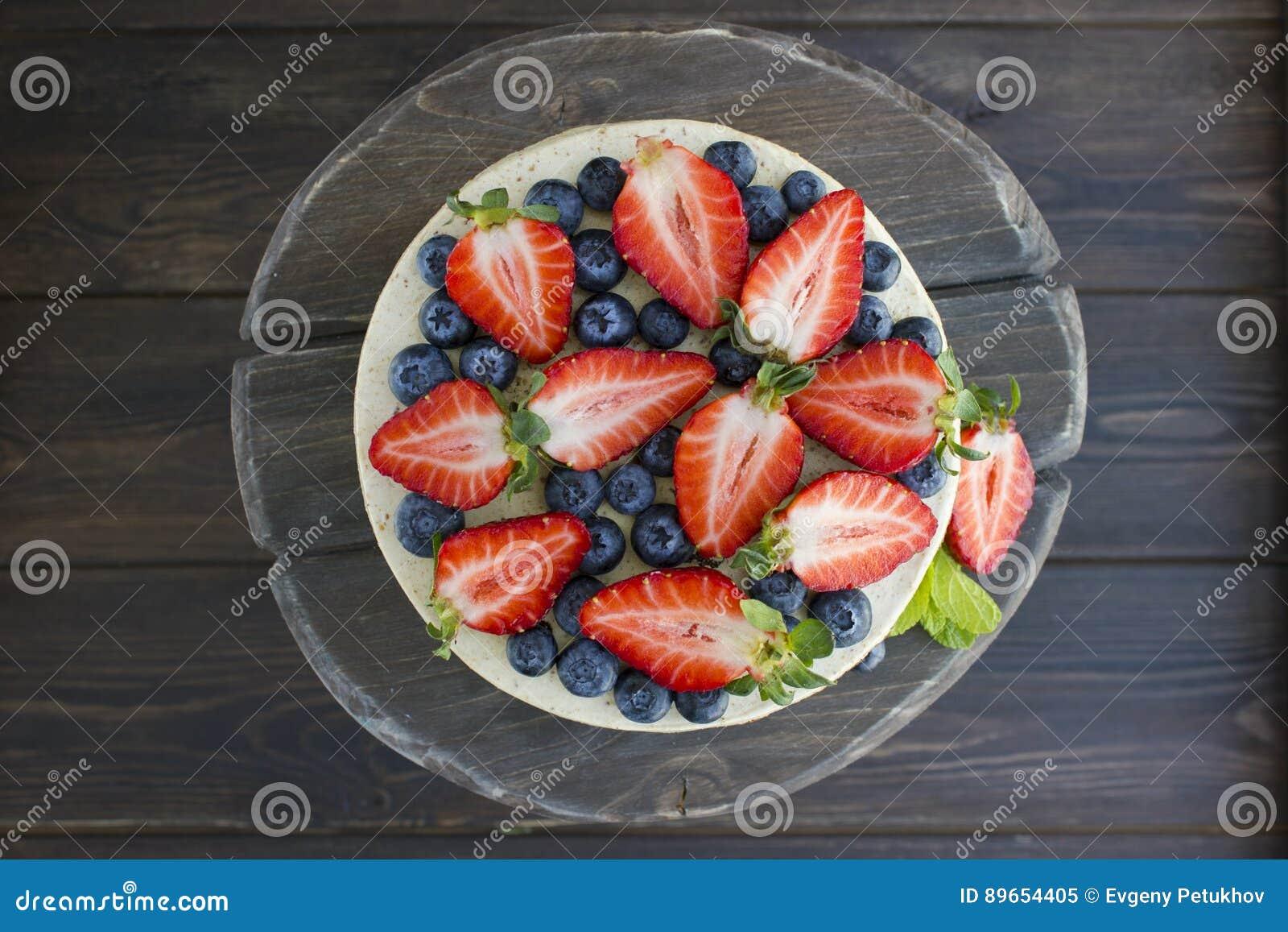 Torta dietética con las bayas en una bandeja de madera Delicioso, útil