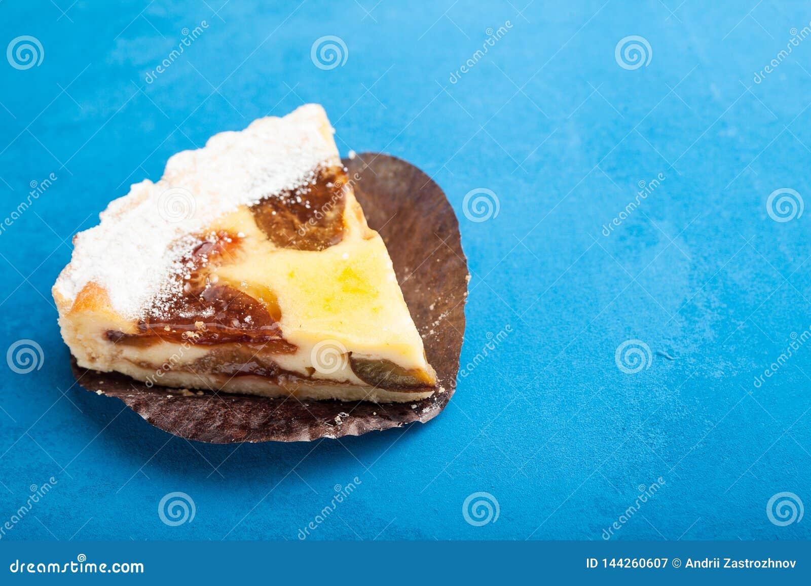 Torta doce delicada do biscoito amanteigado da sobremesa com ameixas em um fundo azul