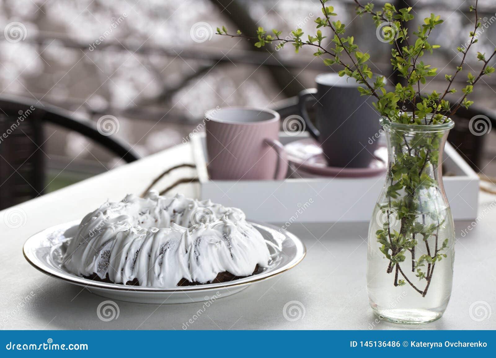 Torta hecha en casa con t? Torta con Sugar Icing Torta hecha en casa bajo la forma de anillo con las tazas de t? o de caf? en la