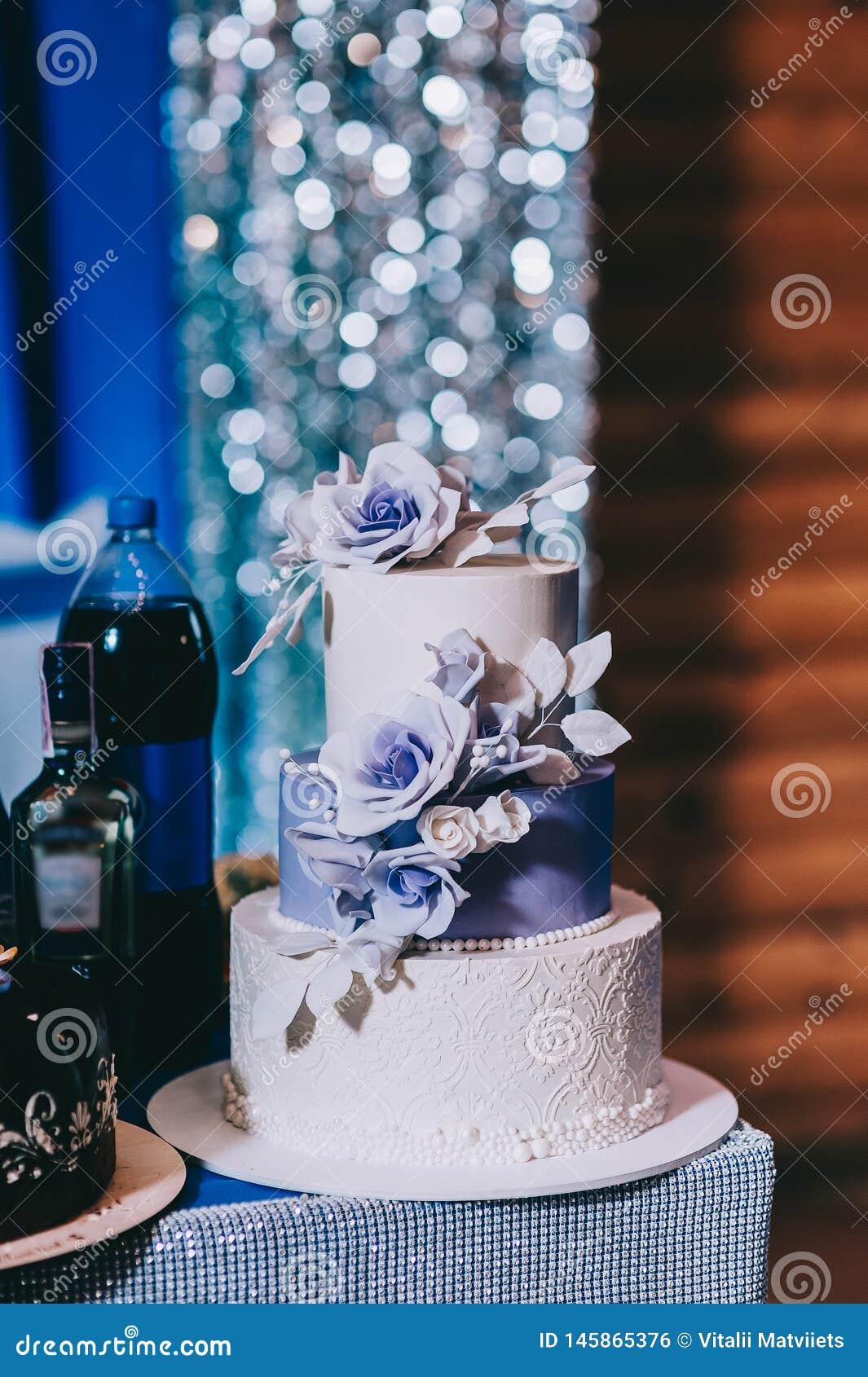Torta nunziale con il blu di turchese rosso beige giallo dei fiori