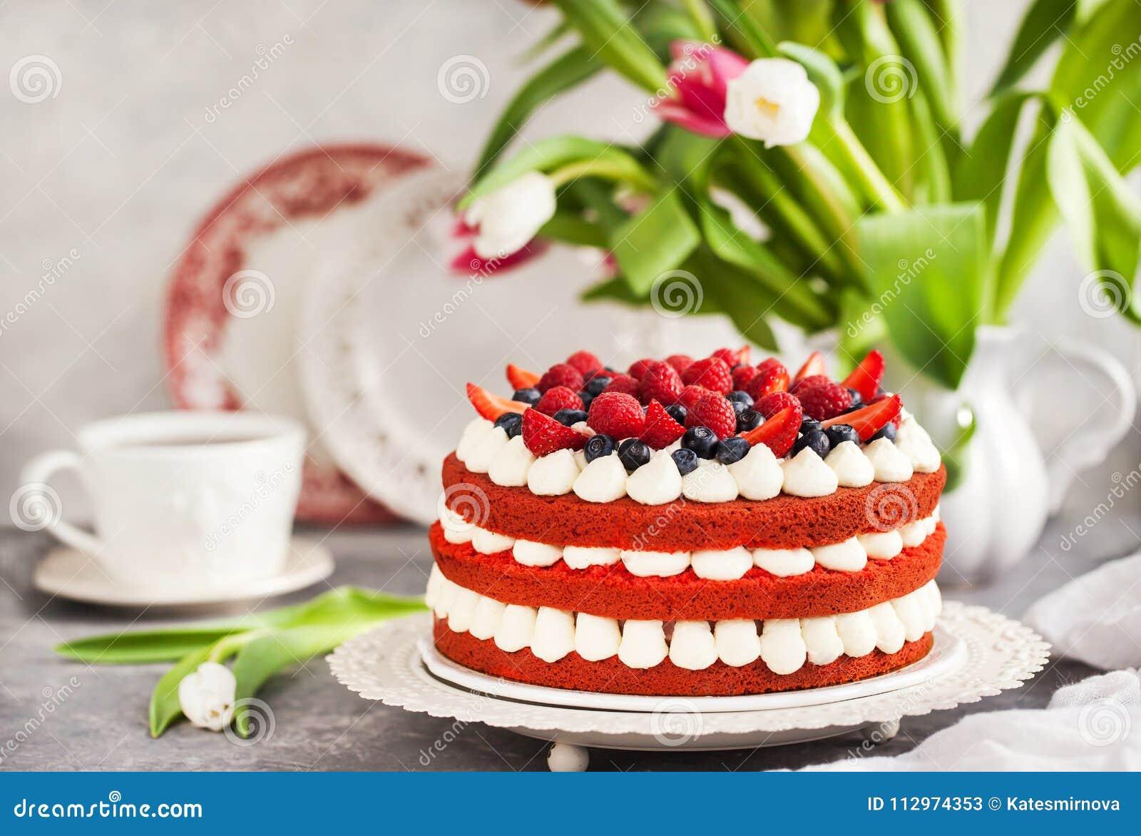 Torta roja hecha en casa deliciosa del terciopelo adornada con crema y fres