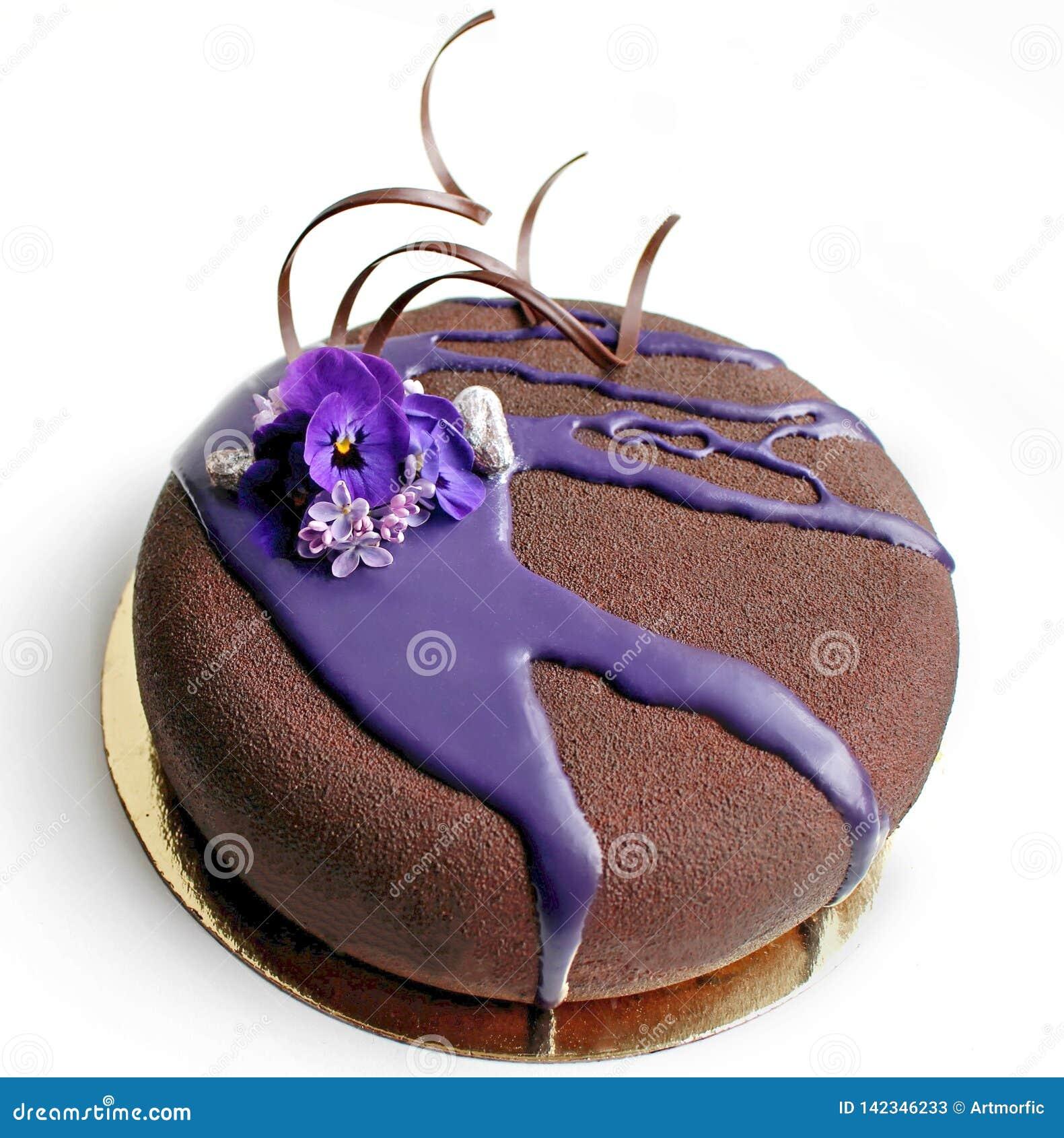 Torta texturizada chocolate de la crema batida con las flores de la primavera y el esmalte púrpura del espejo
