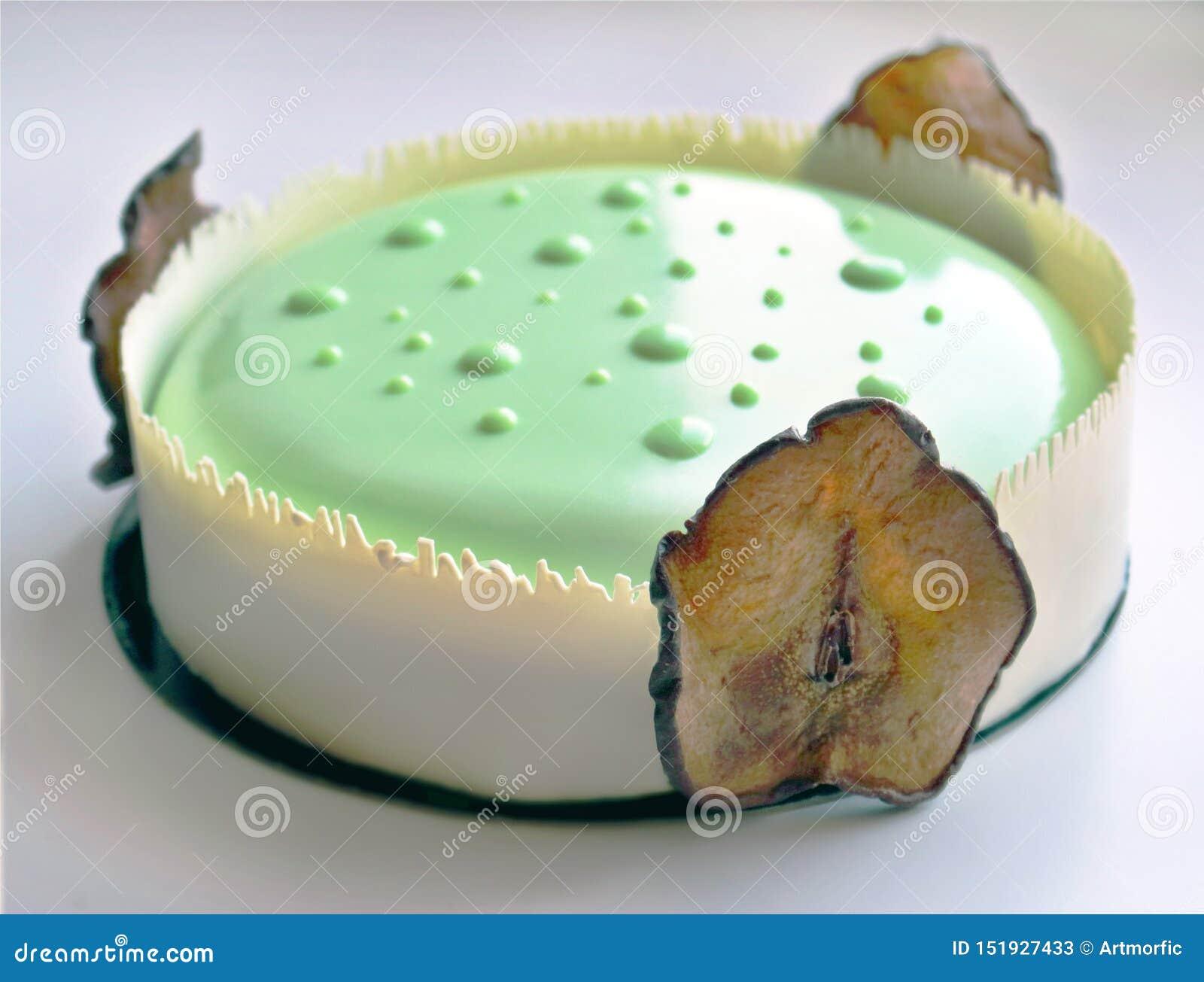 Torta verde clara sensual de la pera con la frontera blanca del chocolate y las peras secadas