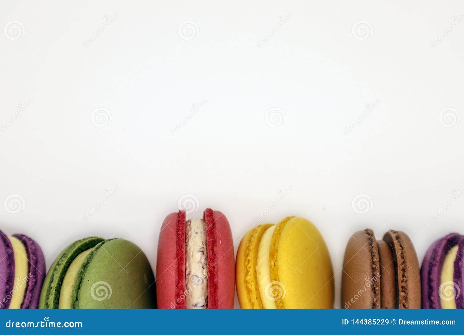 Tortas coloridas de los macarrones en fondo anaranjado