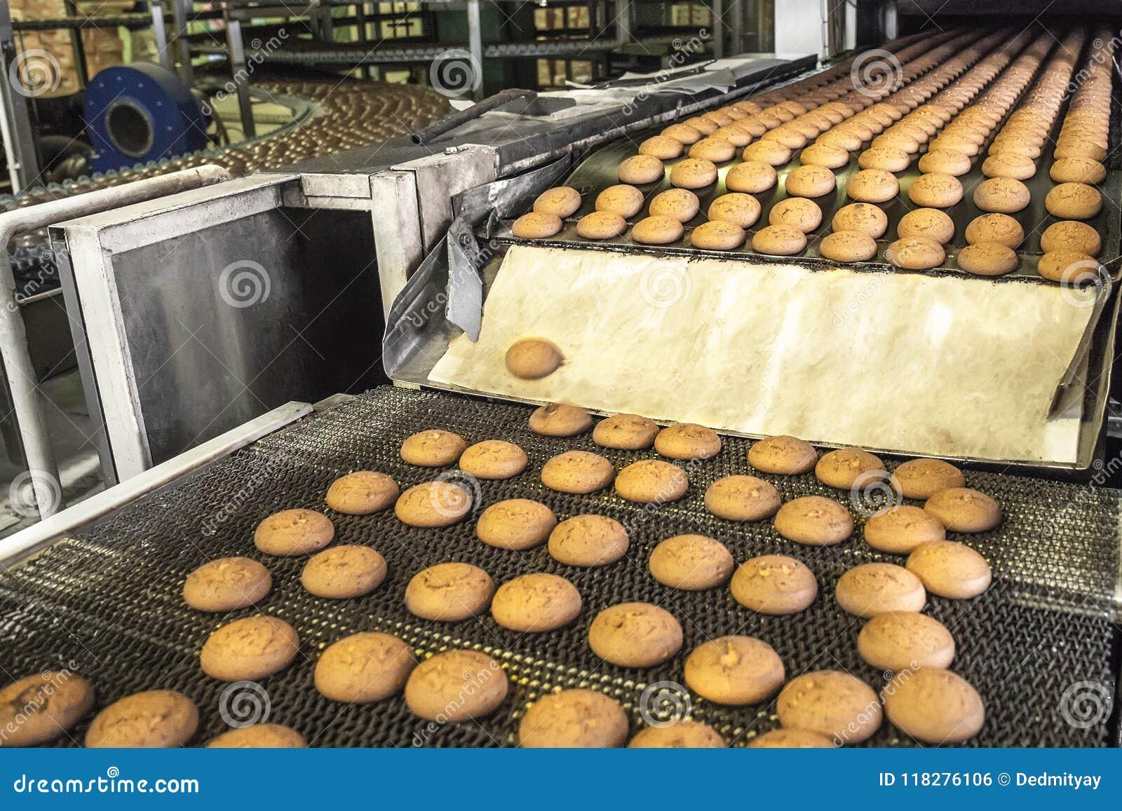 Tortas en la banda transportadora o la línea automática, proceso de la hornada en fábrica de la confitería Industria alimentaria,