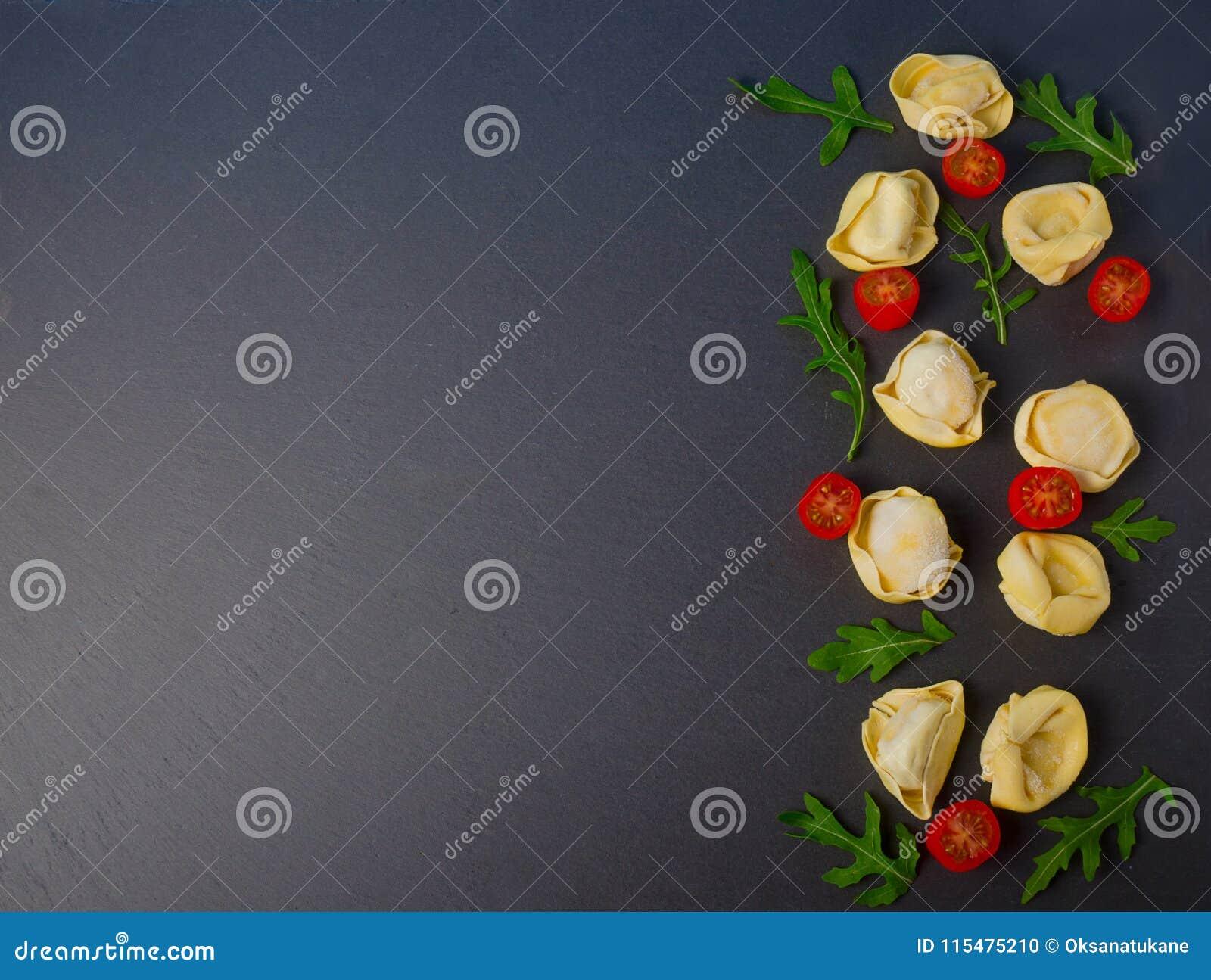 Tortellini congelado no fundo preto Tortellini italiano com as folhas e os tomates frescos da ricota em uma placa de pedra preta