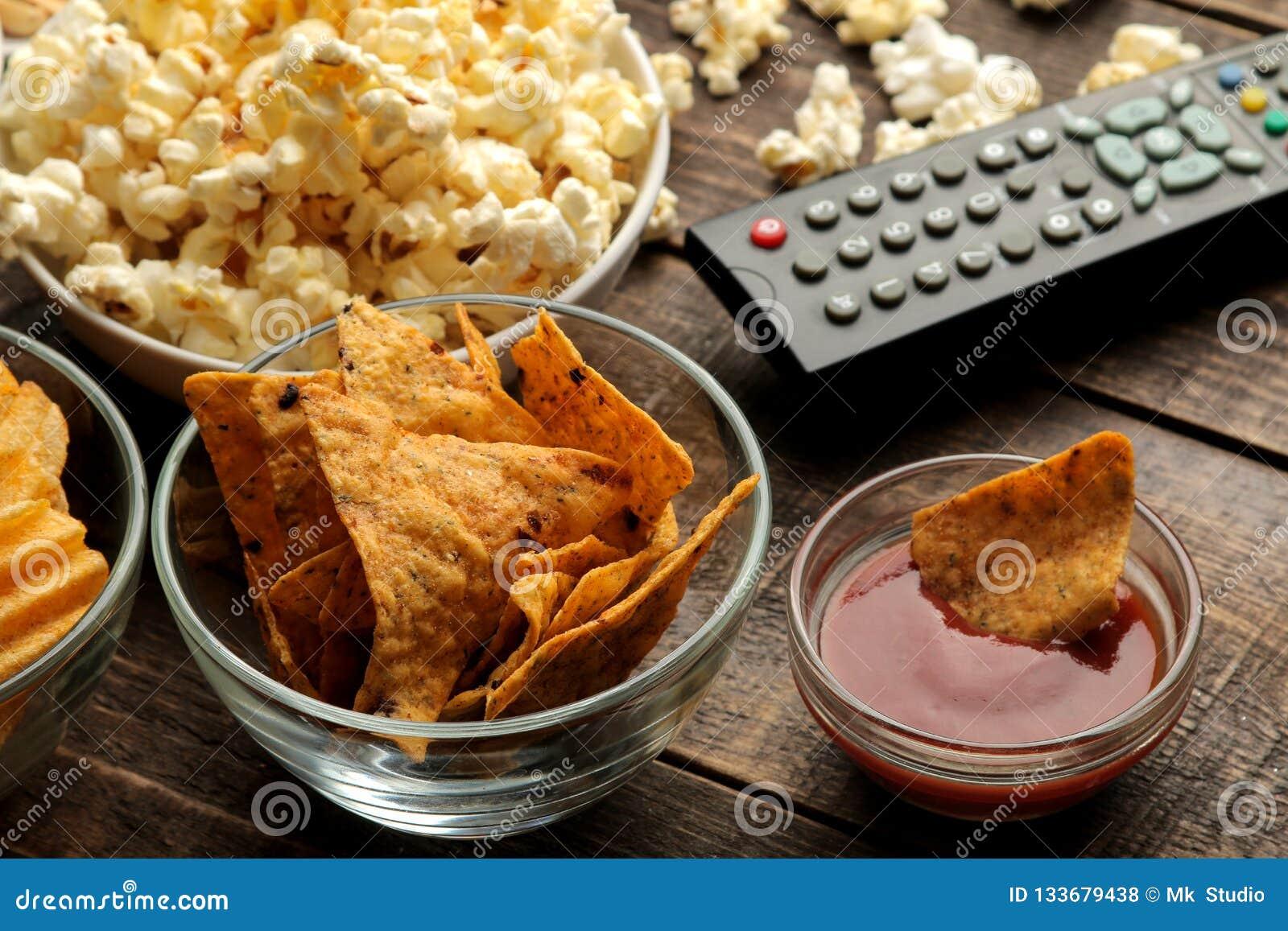 Tortilla и попкорн, ТВ удаленное на коричневой деревянной предпосылке концепция смотреть фильмы дома Конец-вверх