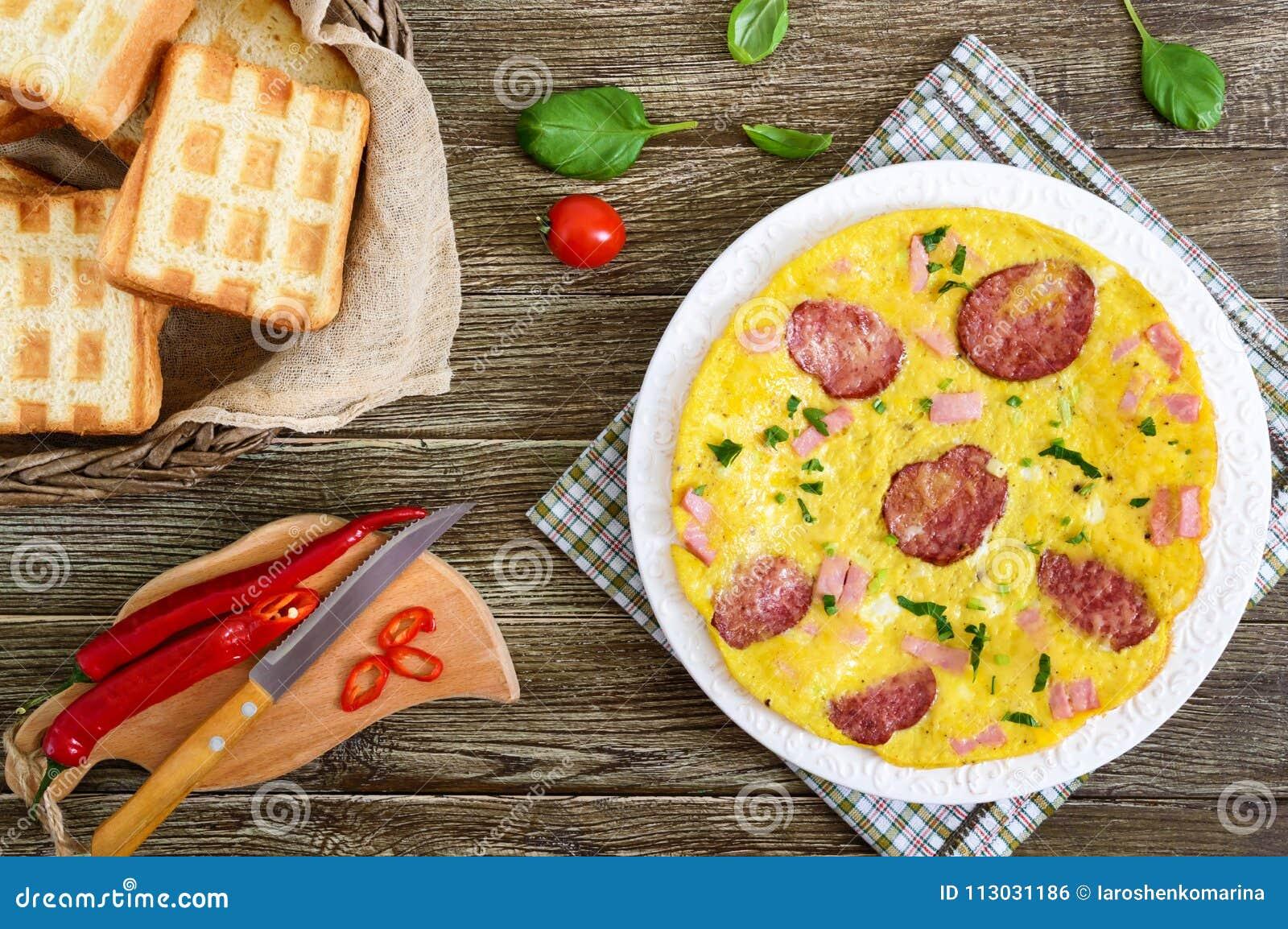 Tortilla con el jamón, el salami, el queso y los verdes en una placa en un fondo de madera