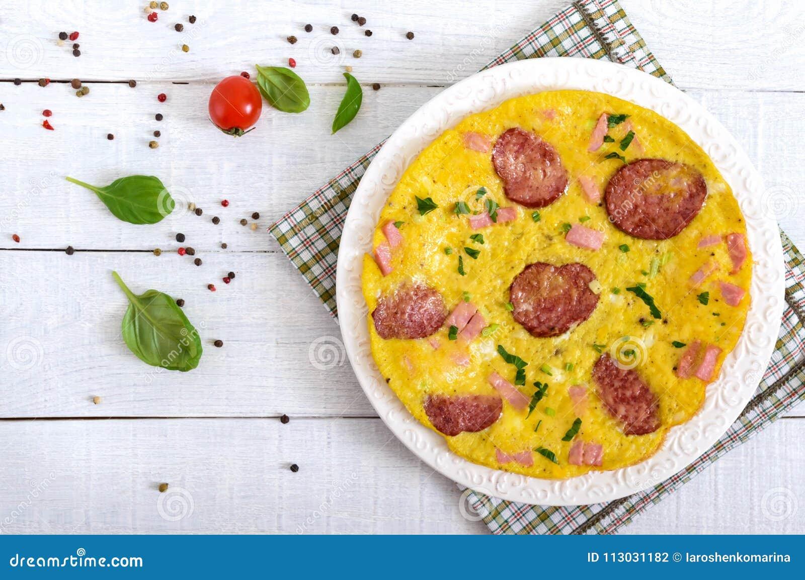 Tortilla con el jamón, el salami, el queso y los verdes en una placa en un fondo de madera blanco
