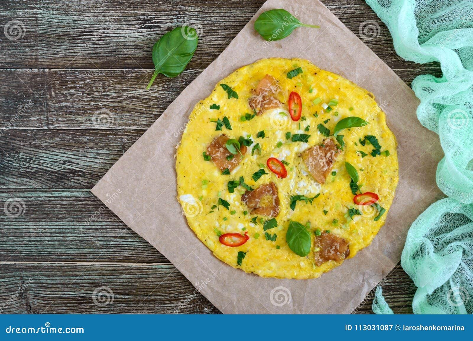 Tortilla con tocino, verdes y queso en una tabla de madera Desayuno
