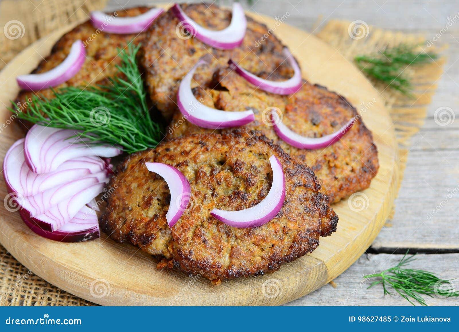 Tortini del fegato di pollo con la carota e la cipolla Tortini casalinghi del fegato di pollo fritto su un tagliere di legno