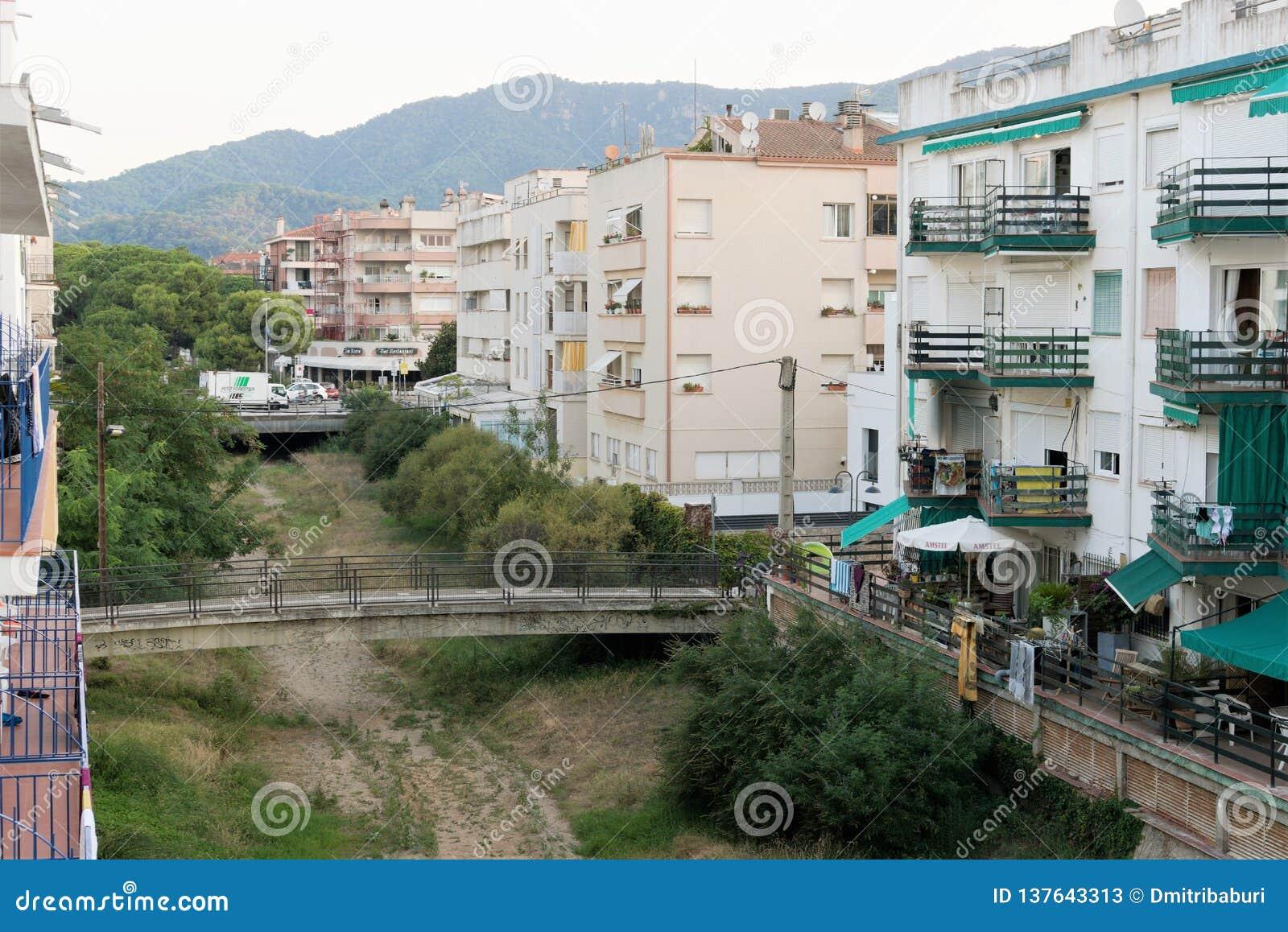 Tossa de Mar, Catalonia, Espanha, em agosto de 2018 Vista da cama de um rio secado-acima com uma ponte e de construções residenci