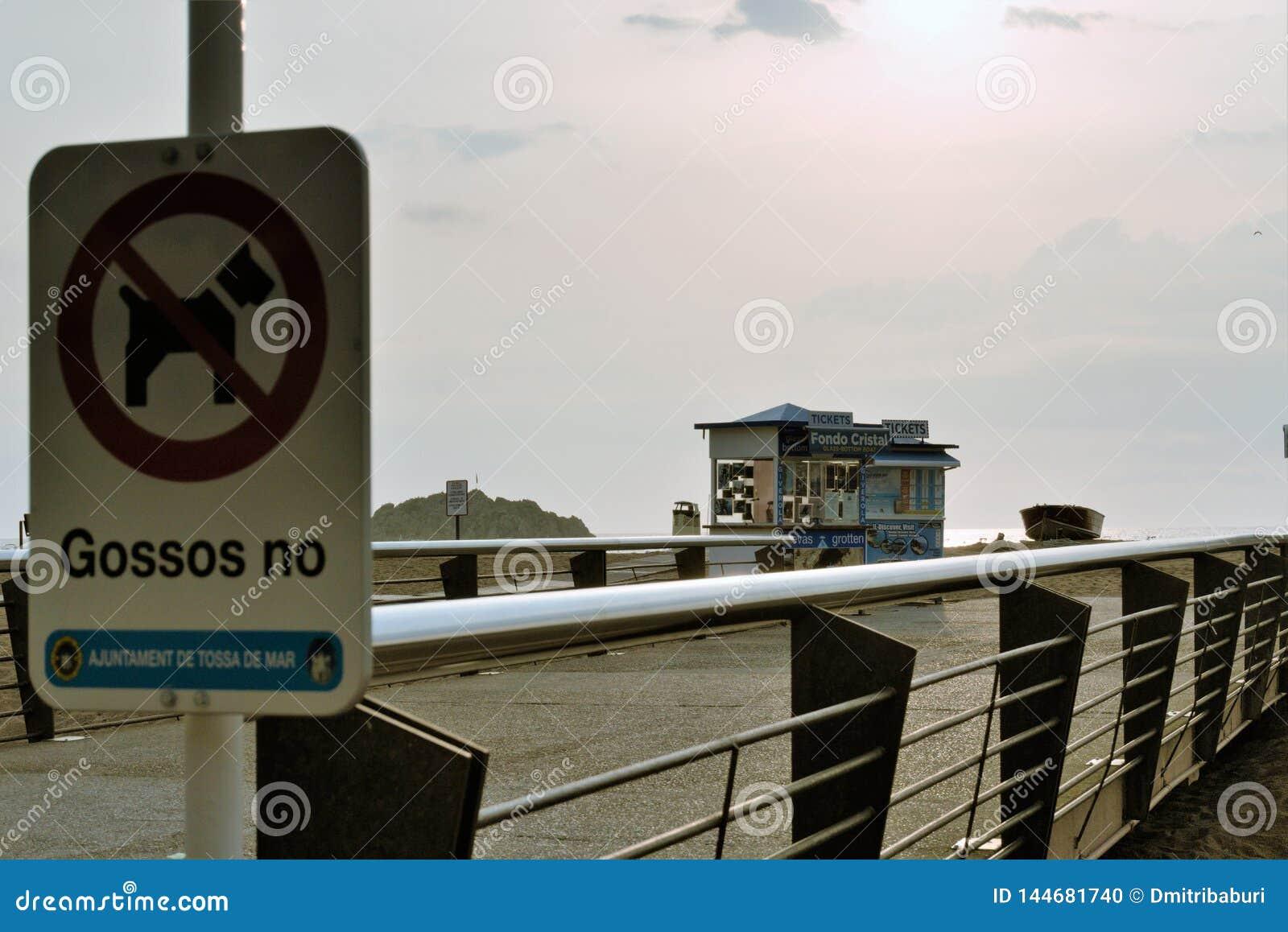 Tossa de Mar, Espanha, em agosto de 2018 Um sinal na proibição do cão que anda na praia no fundo do alvorecer