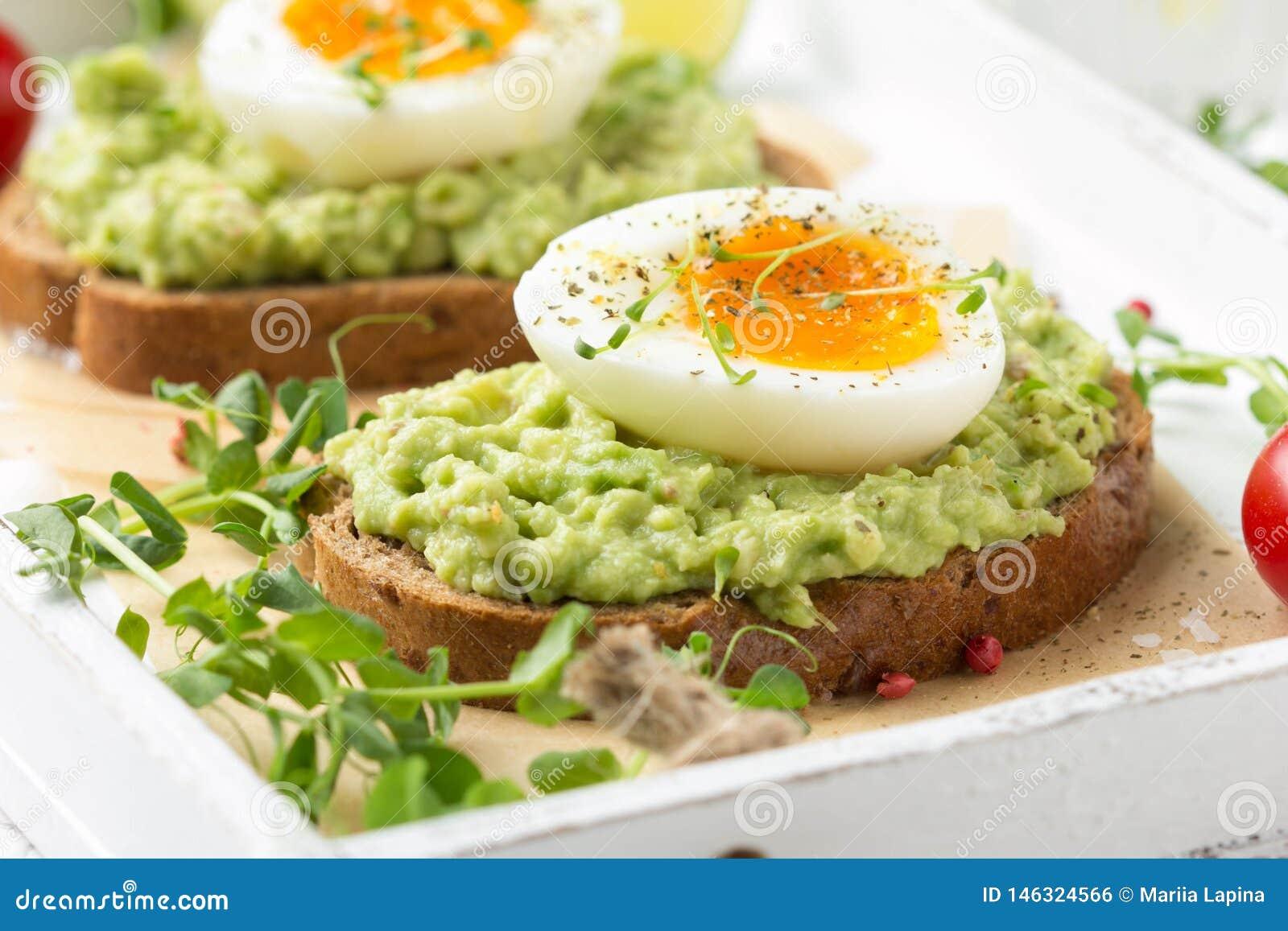 Tostada con puré del aguacate y el huevo pasado por agua en la bandeja blanca, yema de huevo líquida, desayuno delicioso, bocadil