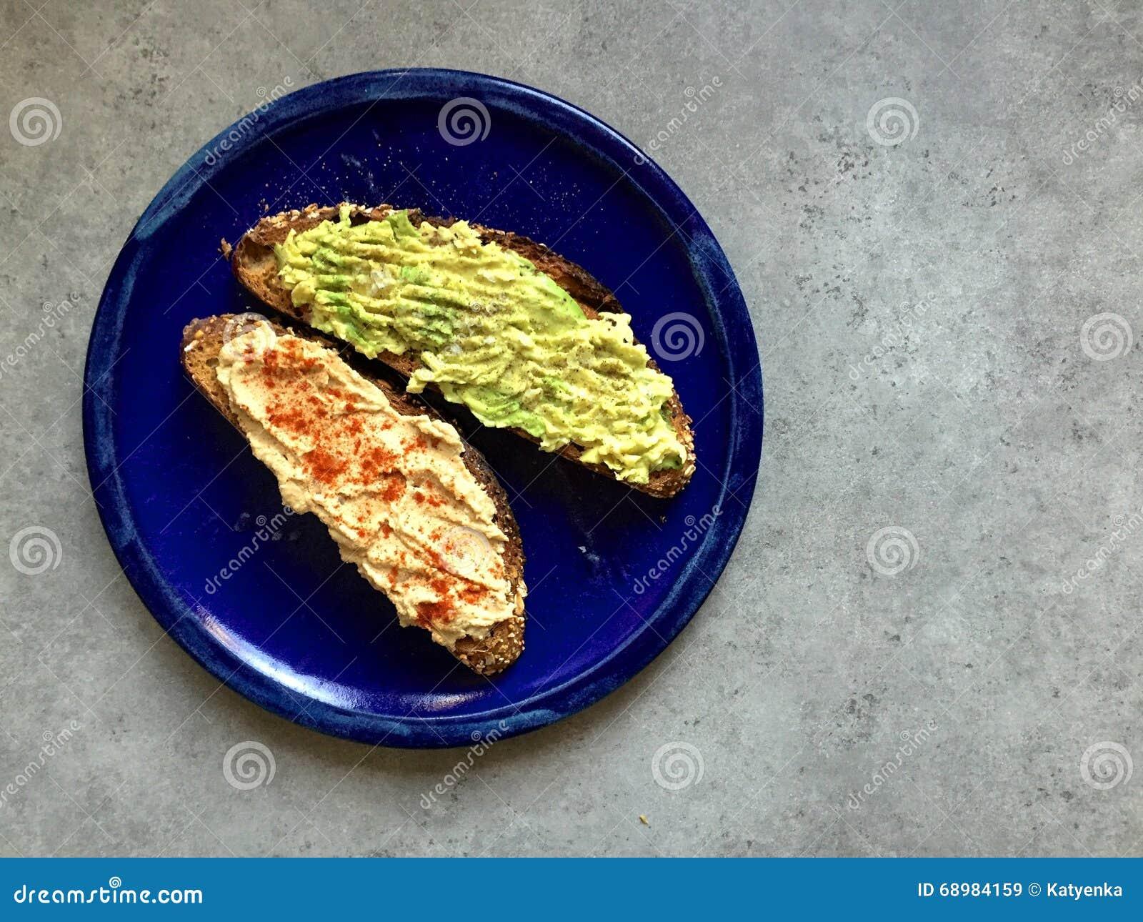 Tostada entera artesanal del grano con el aguacate y el hummus rotos