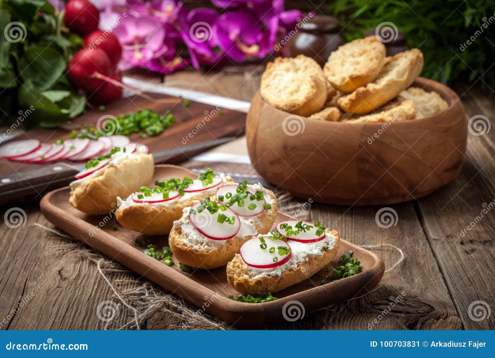Tostadas con el rábano, las cebolletas y el requesón