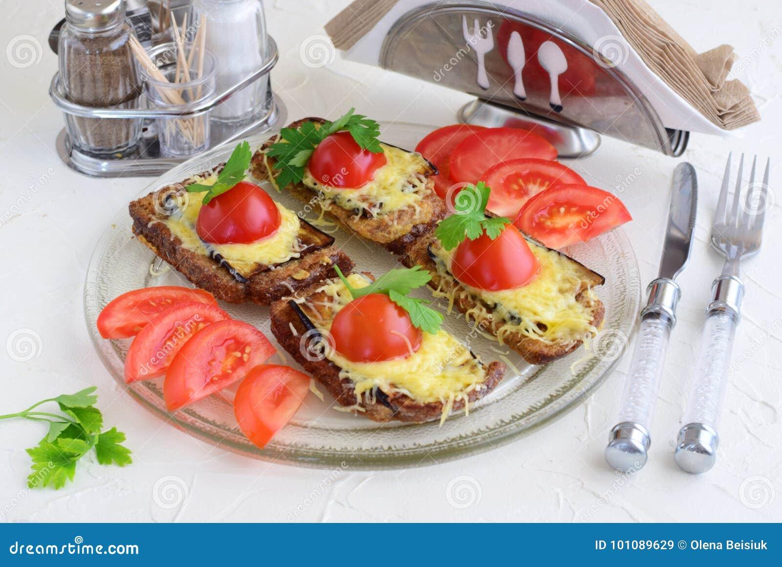 Tostadas con la berenjena, el queso y el tomate en una placa de cristal