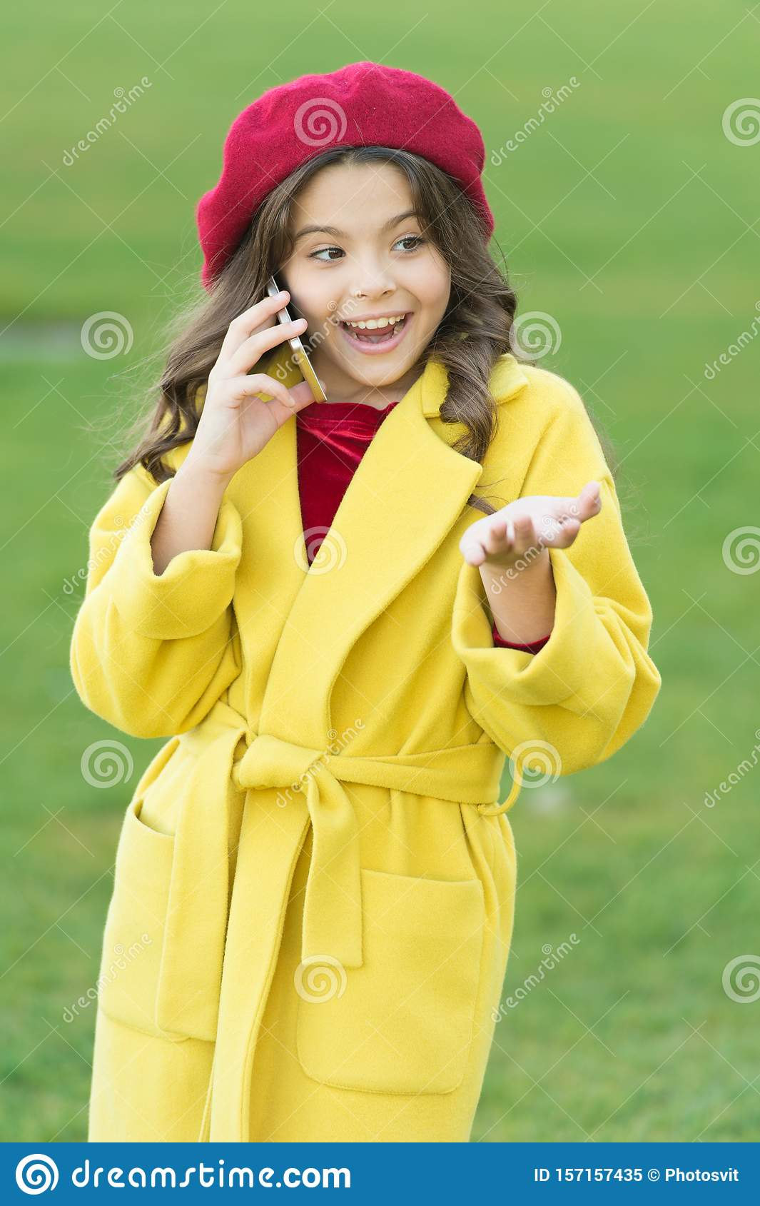 Totally happy. fall season. happy childhood. small child with phone. beauty in autumn coat. cheerful little girl in