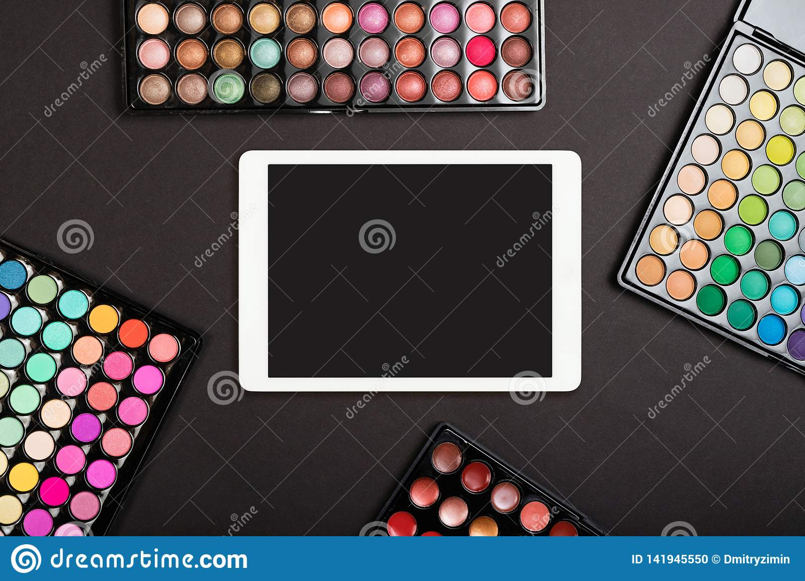 Touchpad with blank screen with colorful eyeshadow palettes on black background. Flat lay