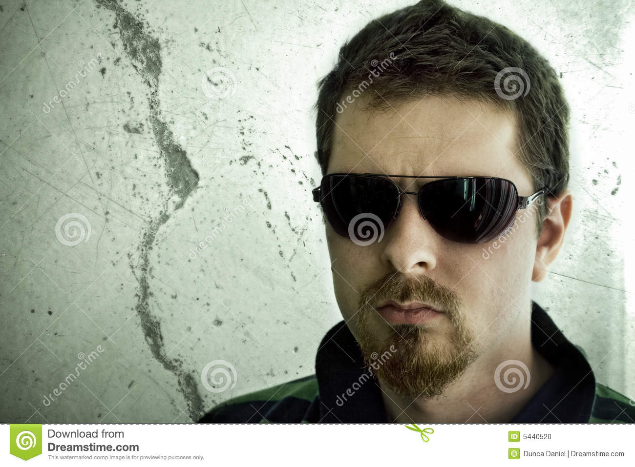 Tough man in front of grunge wall