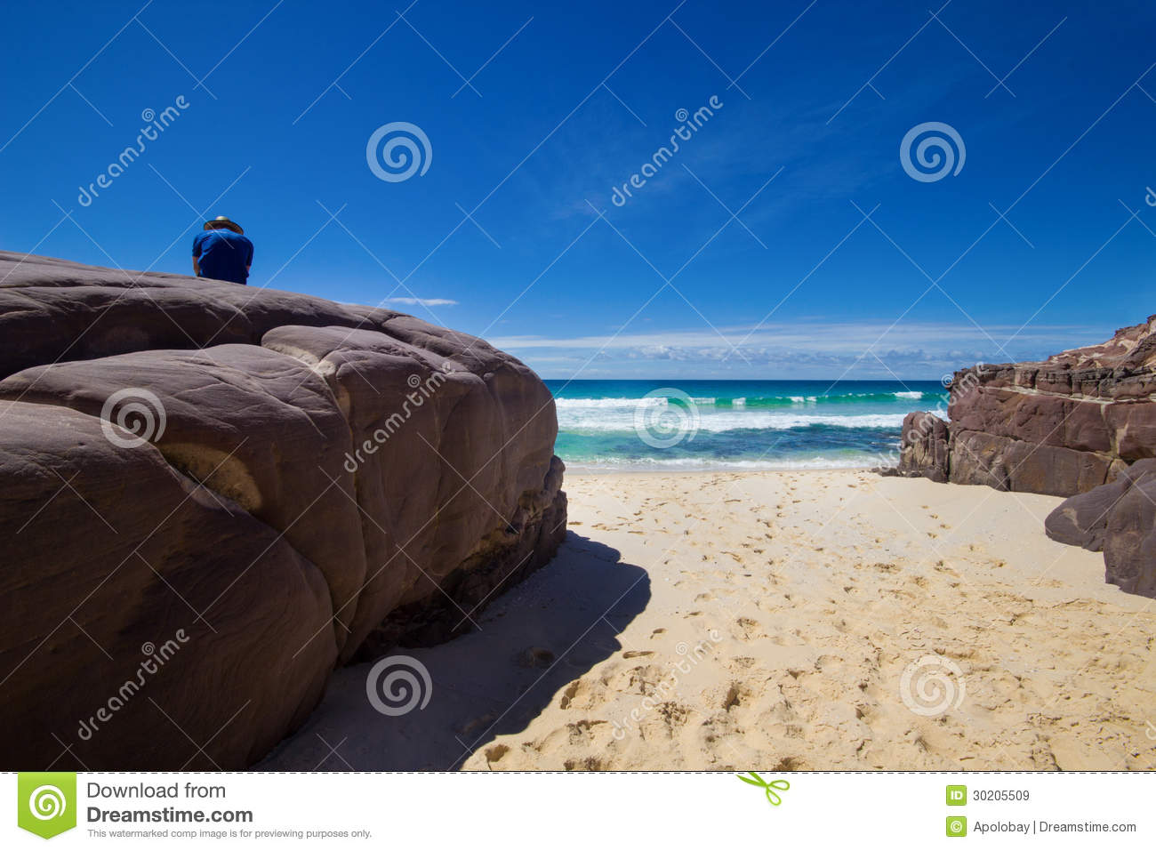 Tourist with backpacks on a large stone and enjoying Sea View. Ben Boyd national park, Australia