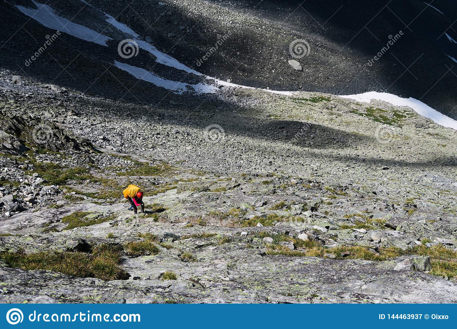 Tourist climbs up the stones in the mountains. Going up the rocky moraine