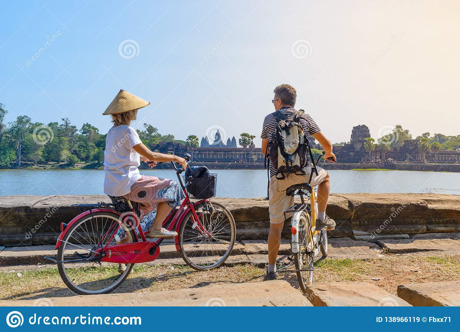 Tourist couple cycling in Angkor temple, Cambodia. Angkor Wat main facade reflected on water pond. Eco friendly tourism traveling