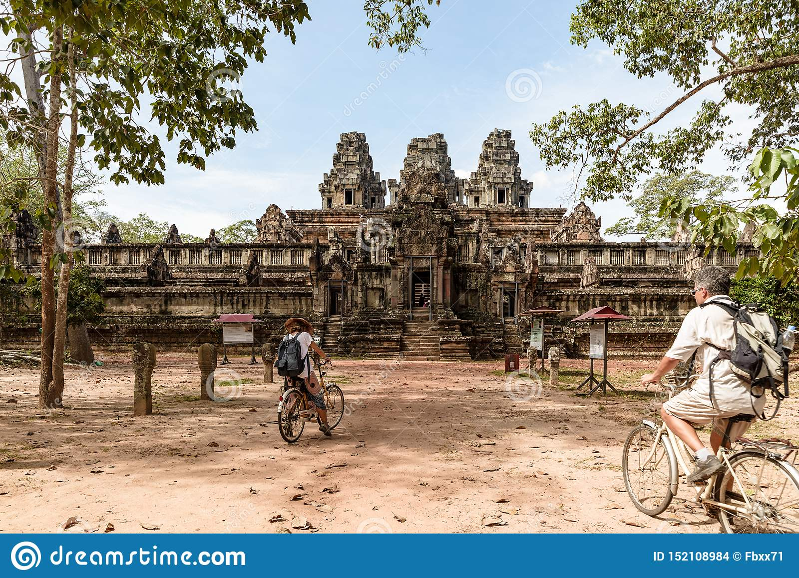 Tourist couple cycling around Angkor temple, Cambodia. Ta Keo building ruins in the jungle. Eco friendly tourism traveling, toned