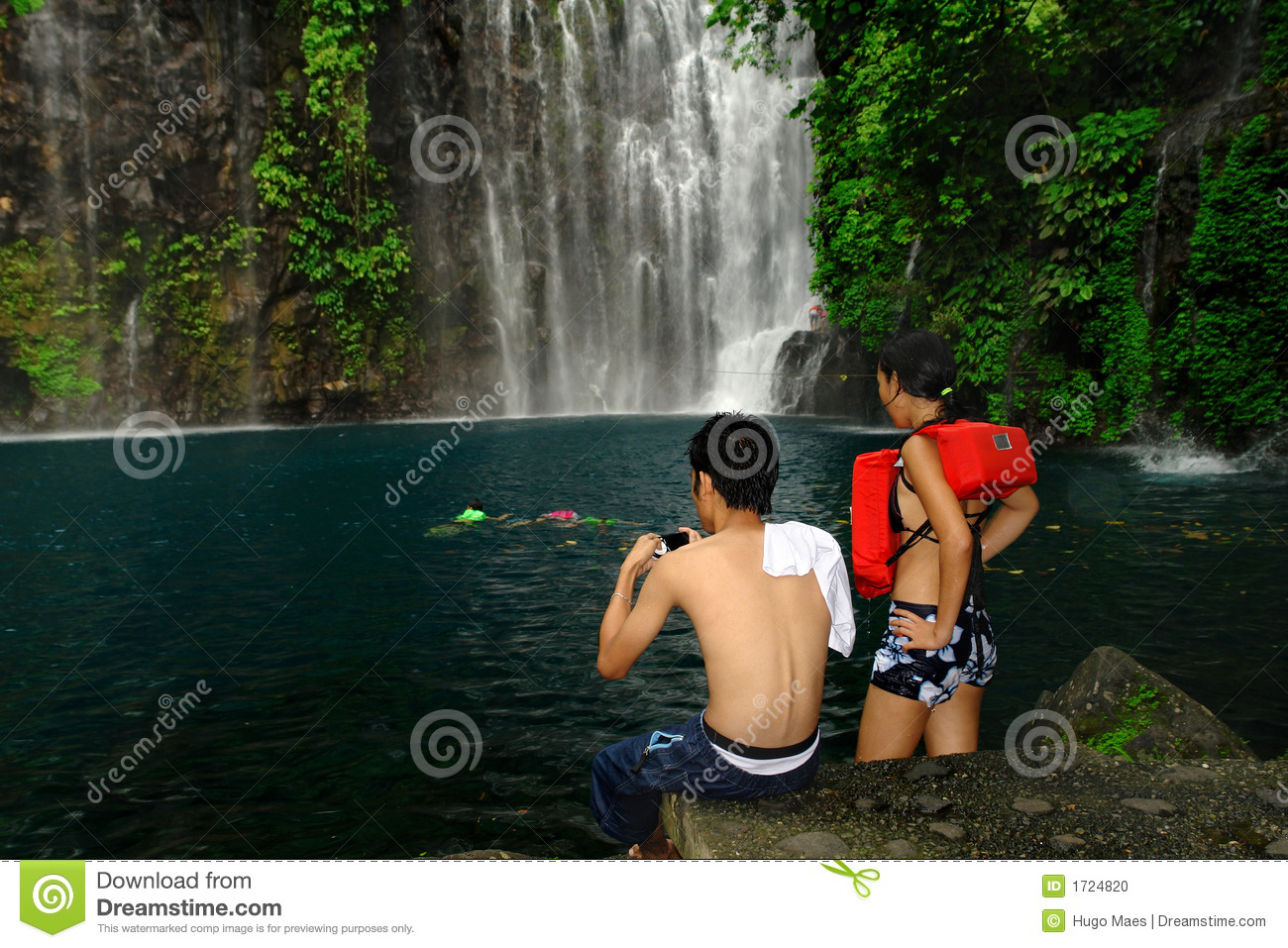 Tourist couple photographing tropical waterfall