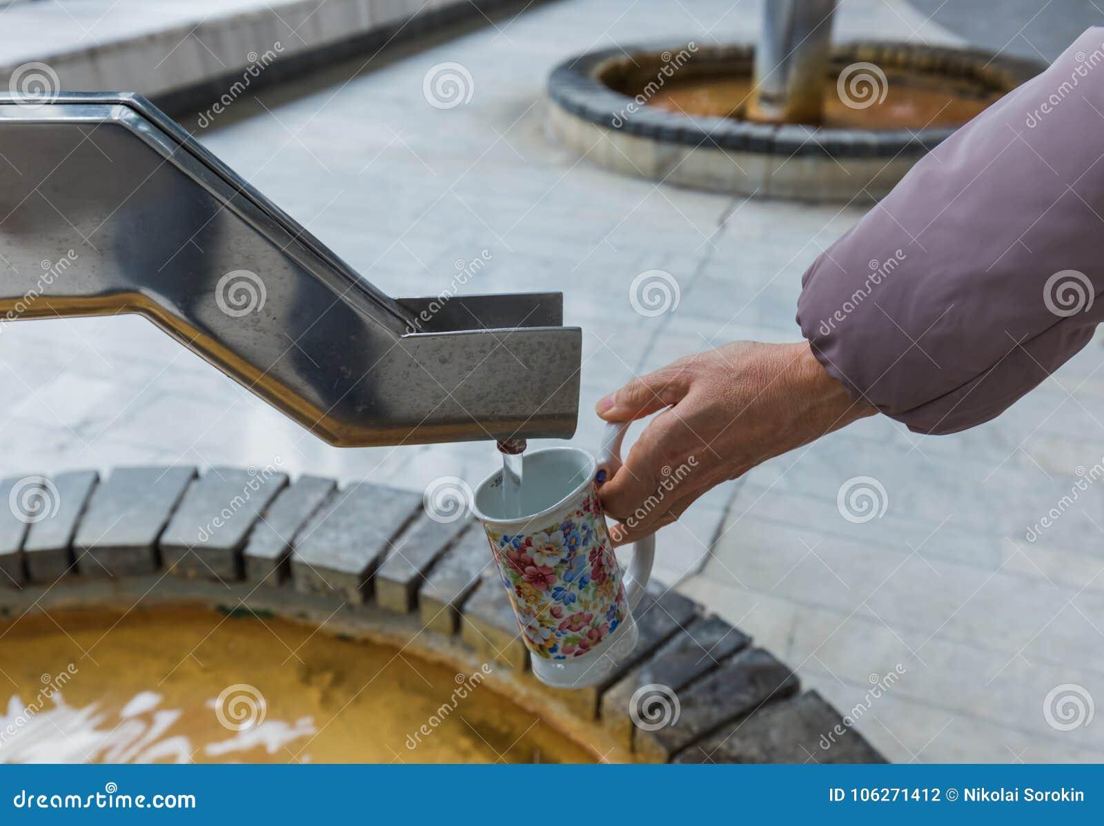 Tourist gießt Mineralwasser von der Quelle in Karlovy Vary - CZ