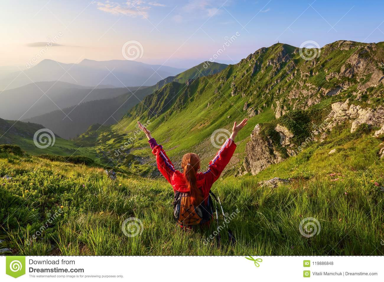 The tourist girl with back sack and tracking sticks sits on the lawn. Relaxation. Mountain landscapes. Wonderful summer day.