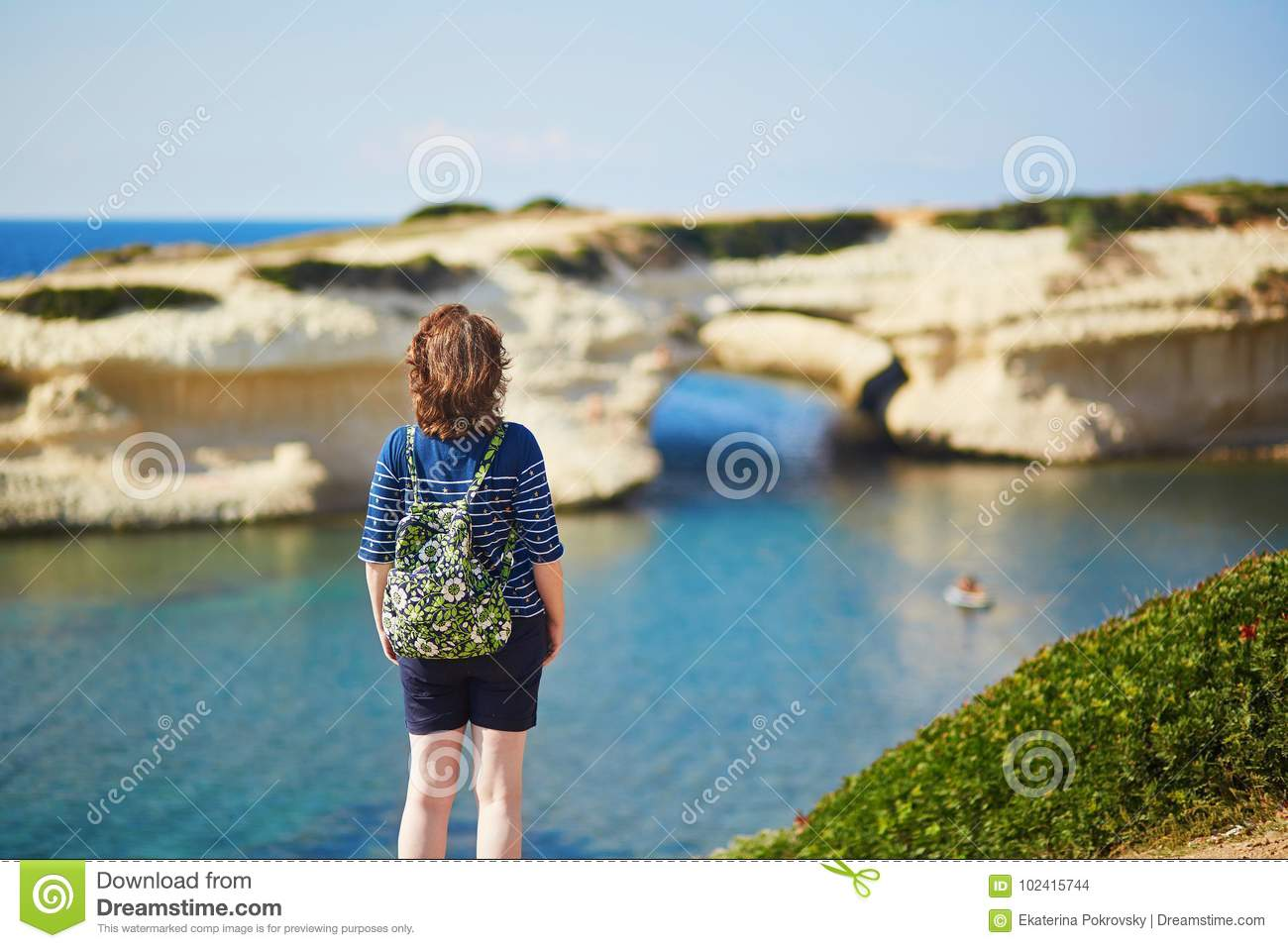 Tourist girl with backpack enjoying beautiful view of natural arch and sea  in Sardinia 201b13ca6e5ce