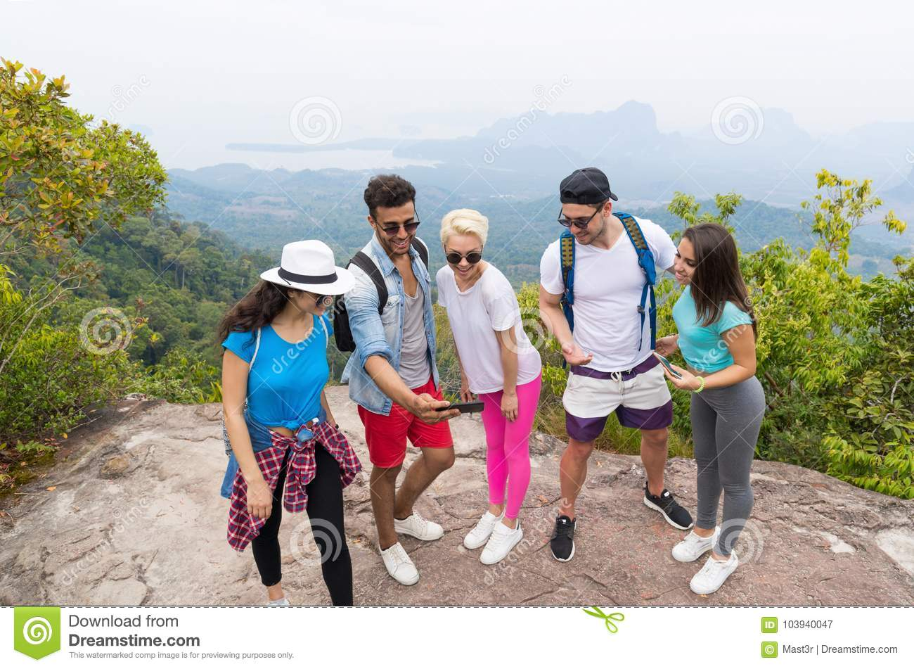 Tourist Group Watch Photos On Cell Smart Phones, People With Backpack Over Landscape From Mountain Top
