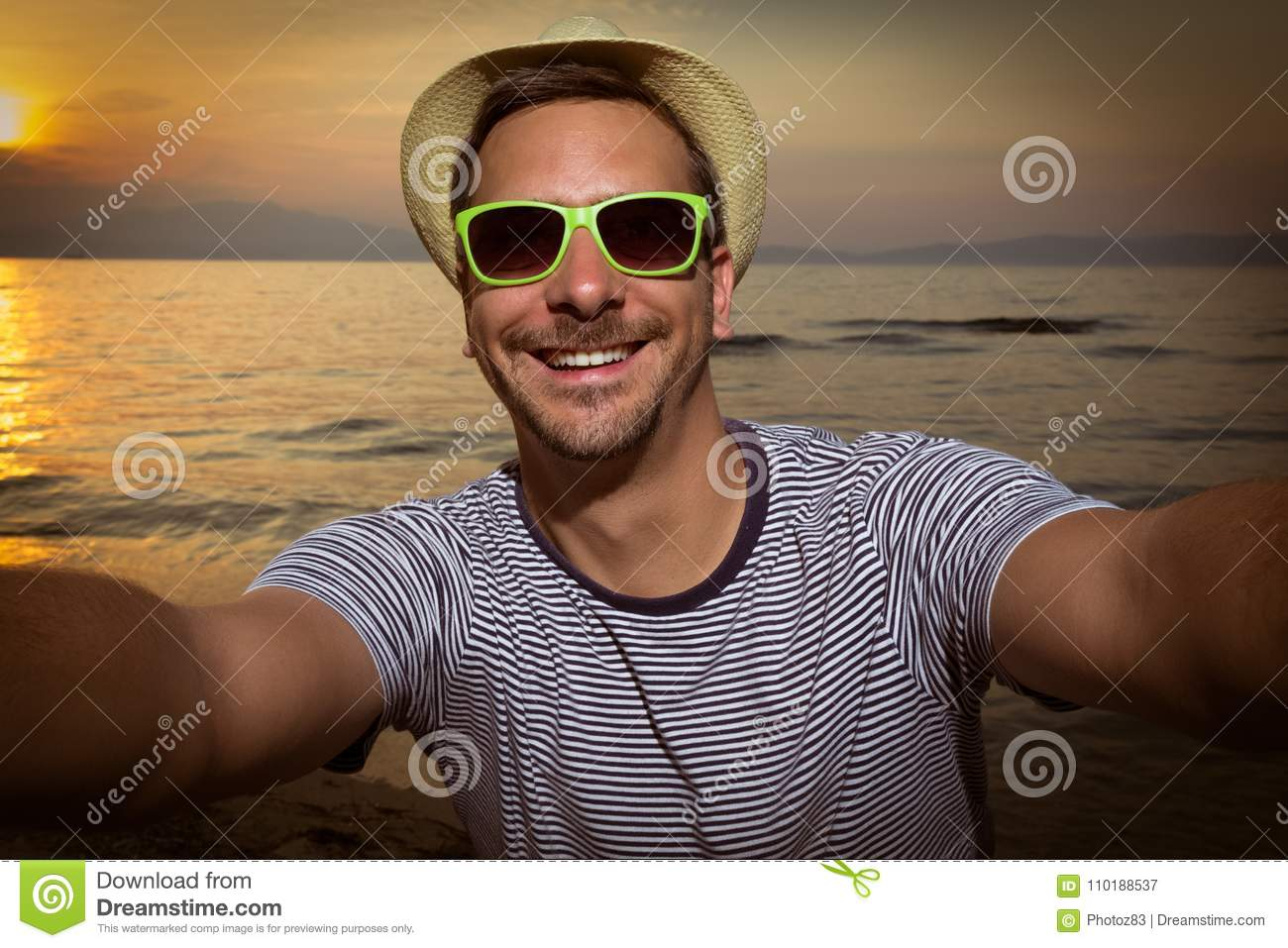 4cea1eab2ec Modern young man with sunglasses and hat making selfie. Sunset over sea and  beach in the background. Travel and tourism concepts.