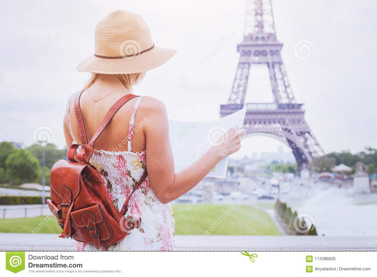 Tourist Looking At The Map Of City Paris Near Eiffel Tower Stock ...