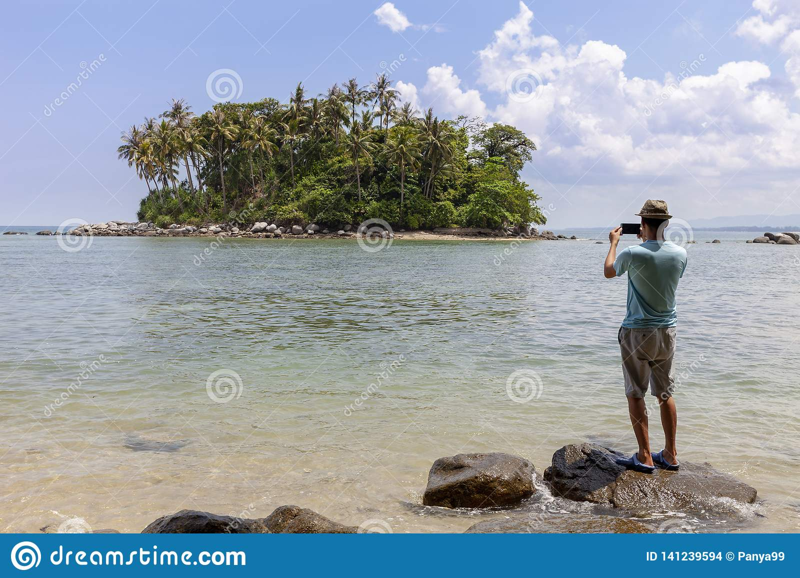 Tourist man standing on the stone in summer season and take a photo beautiful small island in phuket thailand