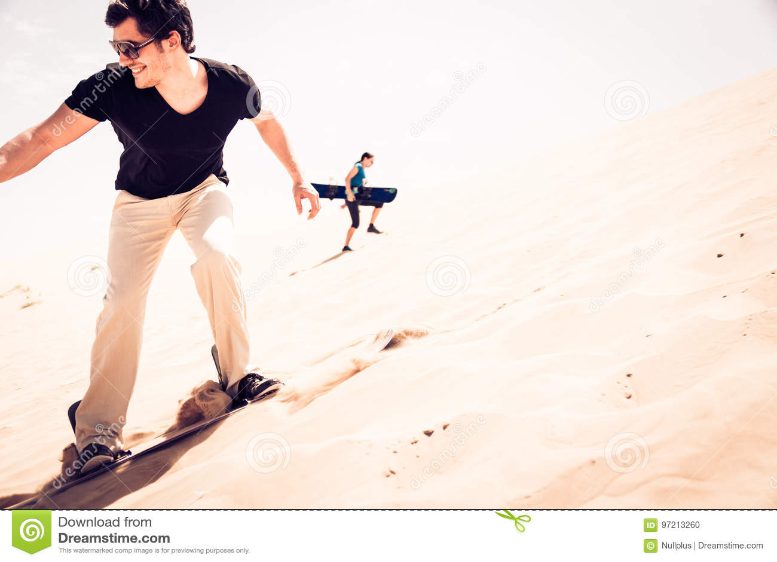 Tourist Sandboarding In The Desert Stock Photo - Image of