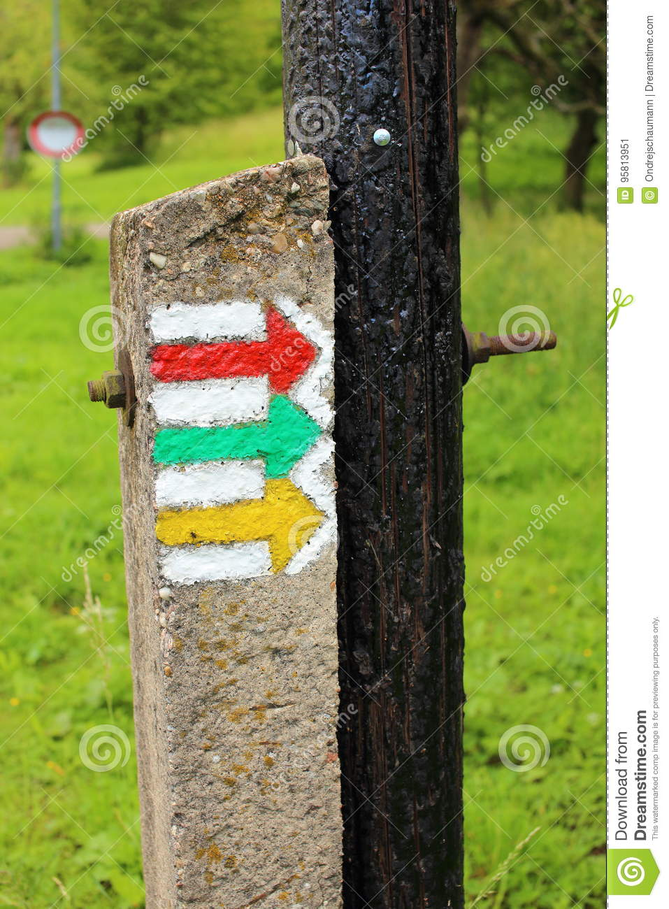 Red green and yellow tourist track signs on the electric pole grounding