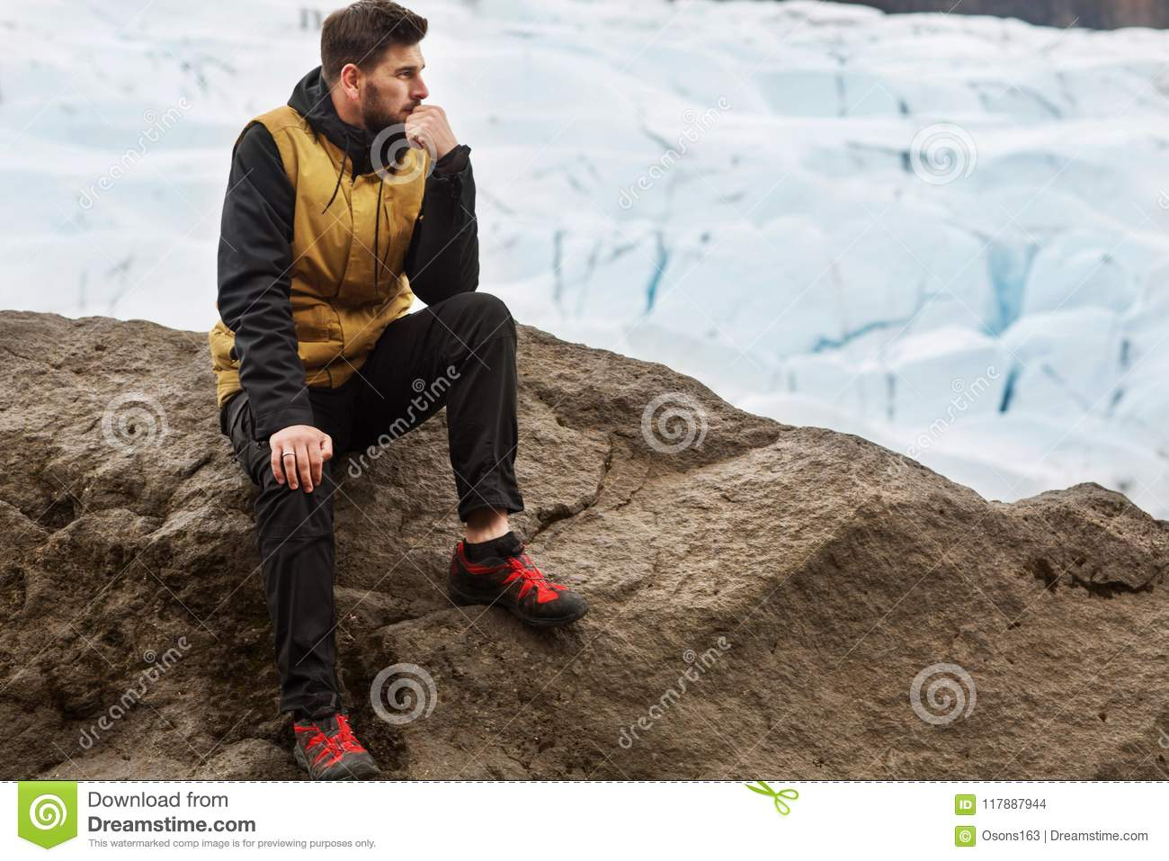 Tourist sits near the glacier iceberg in Iceland