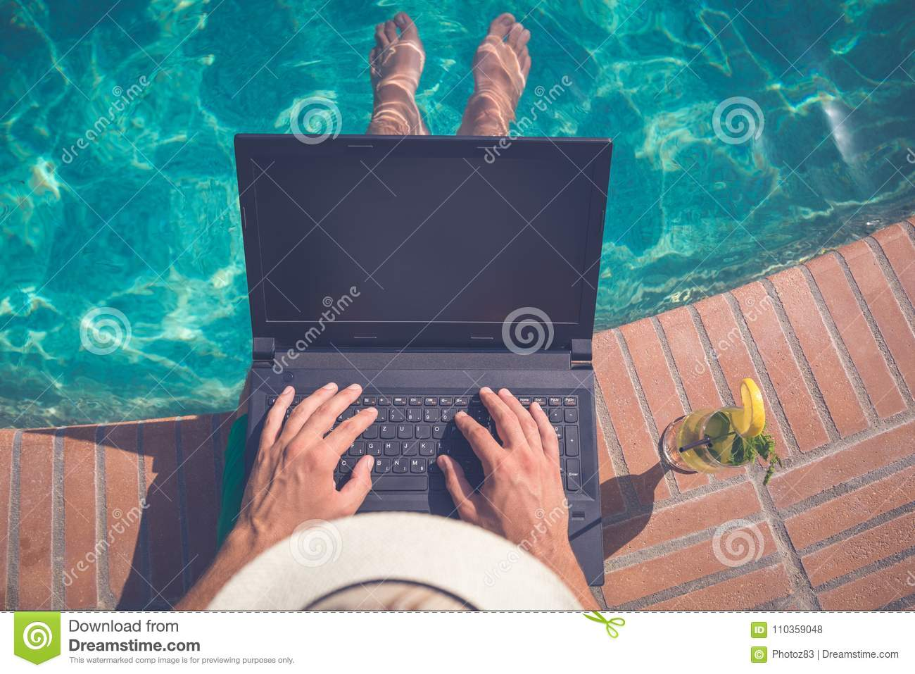 95fccf2c8e7ee High angle view of man sitting at the poolside and using laptop. Travel and  technology concepts