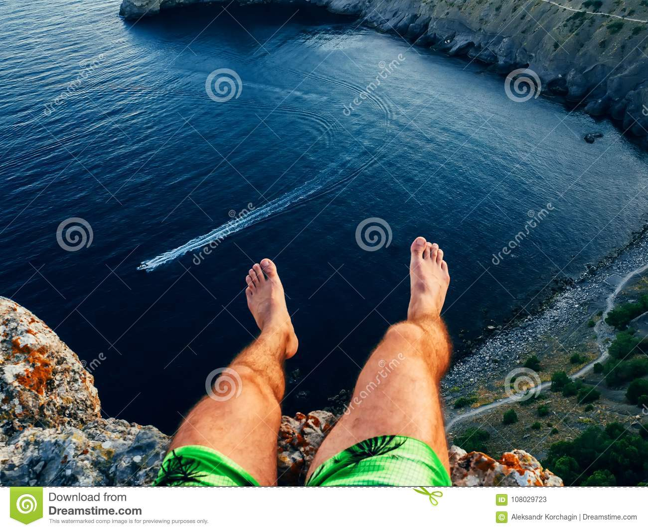 Tourist sitting on top of mountain above sea dangling feet outdoors